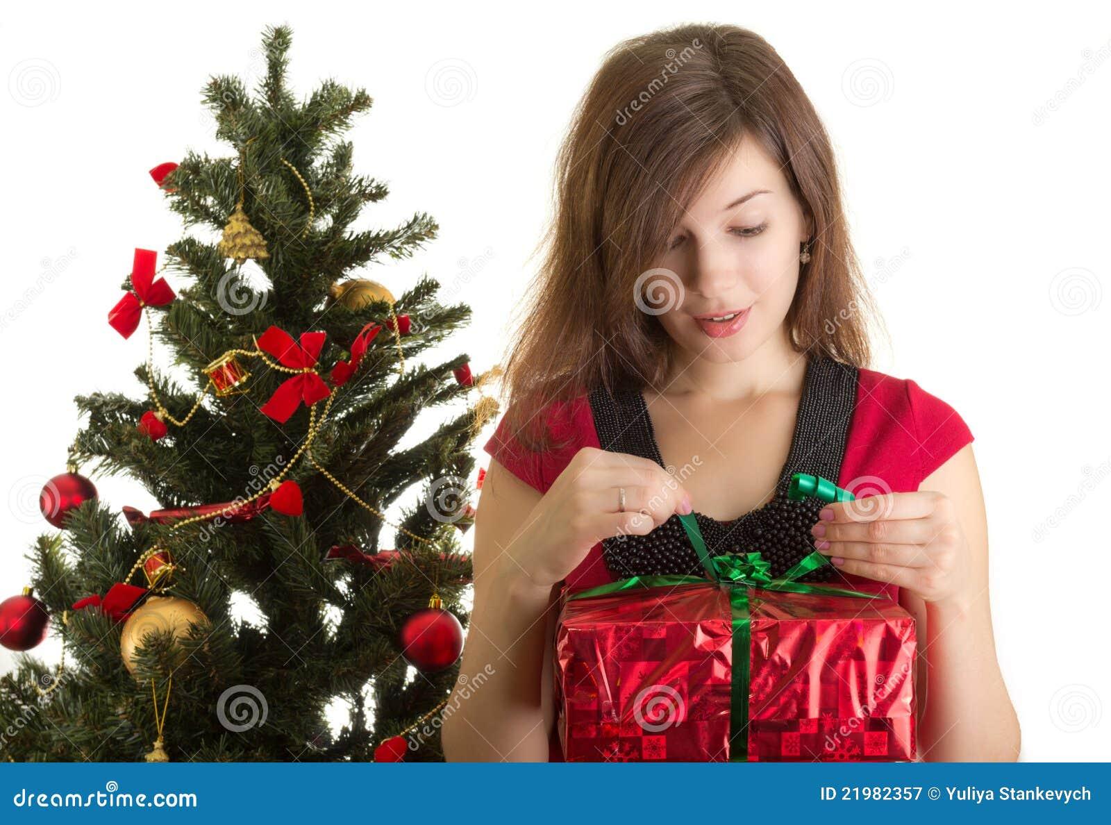 Cadeau d ouverture de femme près d arbre de Noël