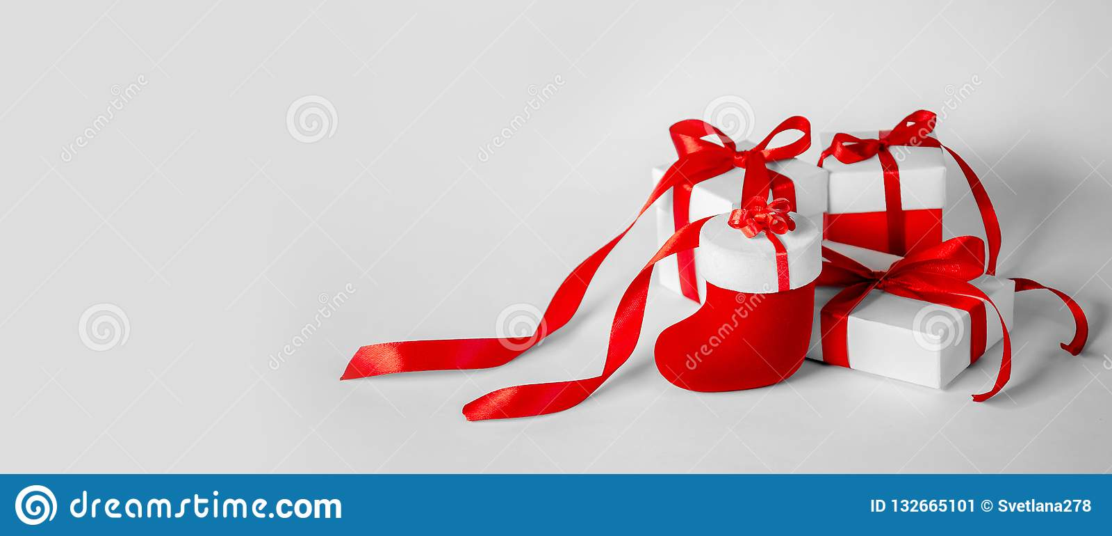 Cadeau de Noël dans le boîtier blanc avec le ruban rouge sur Backgroun léger