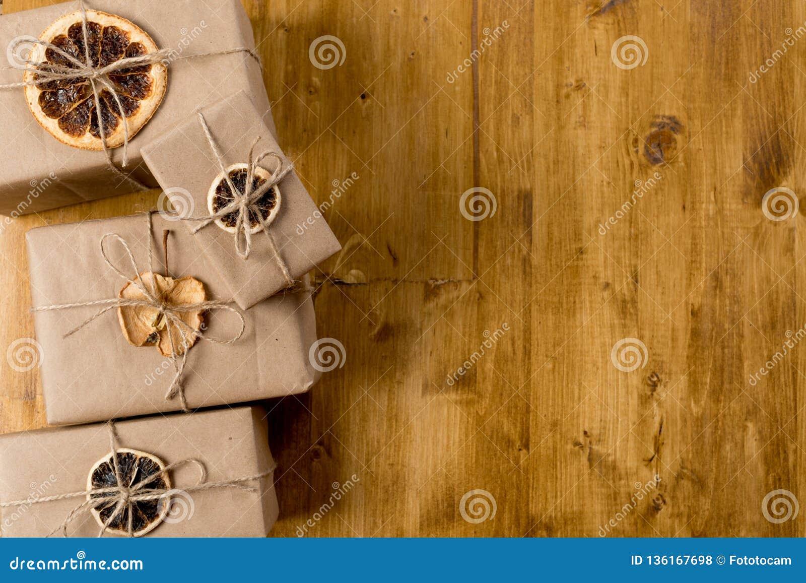 Cadeaux décorés de l agrume sec sur la vue supérieure de fond en bois