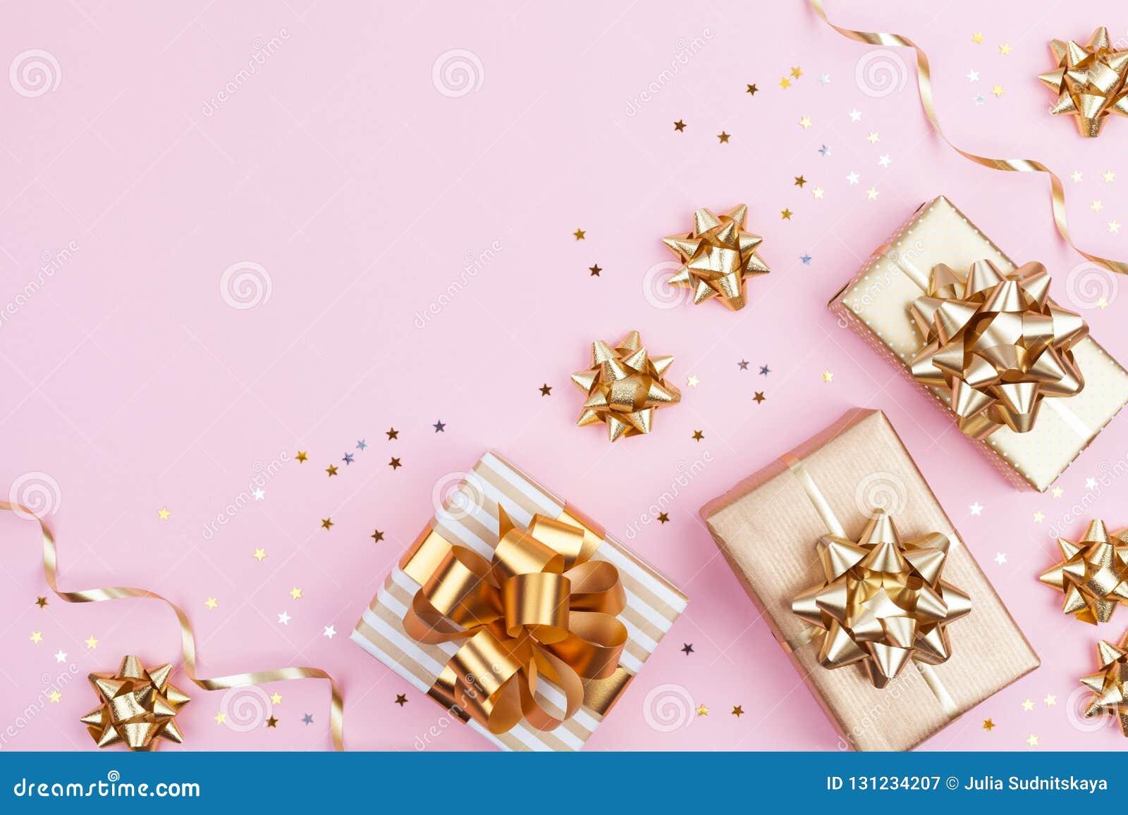 Cadeaux de mode ou boîtes de présents avec les arcs d or et confettis d étoile sur la vue supérieure de fond en pastel rose Confi