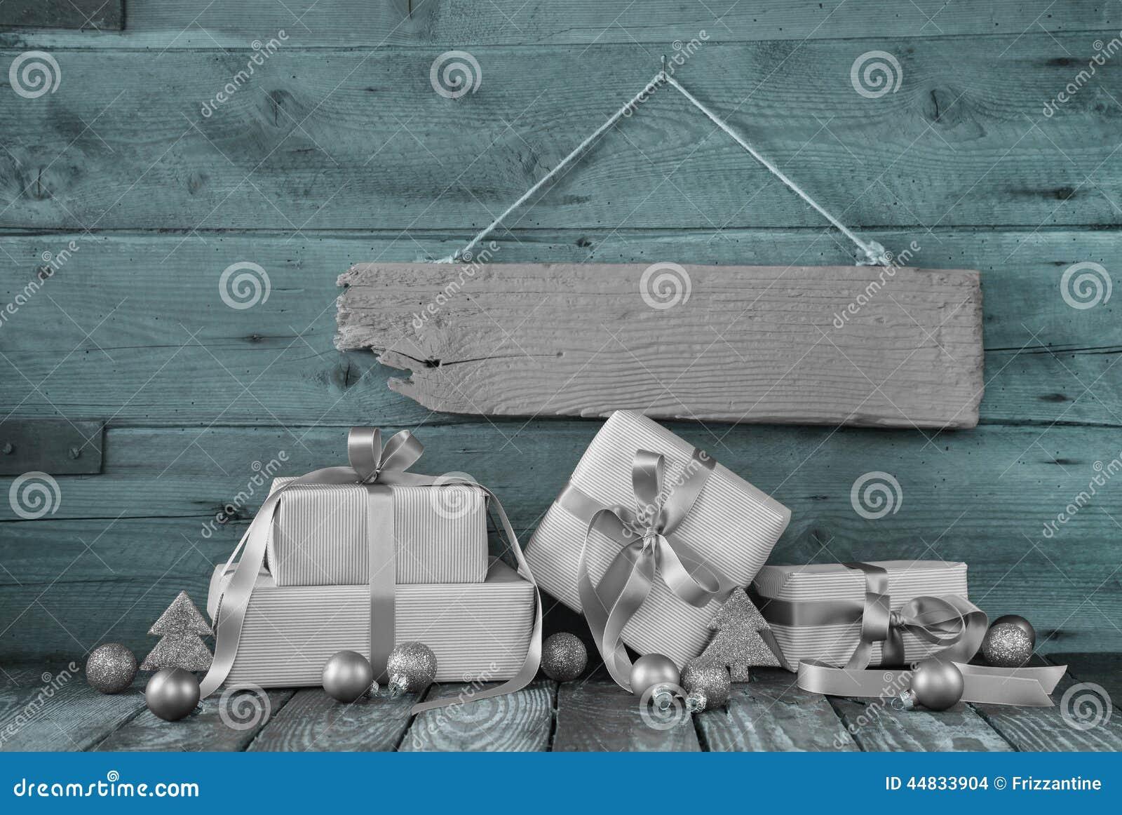 Cadeaux de Noël argentés sur le fond en bois avec un signe