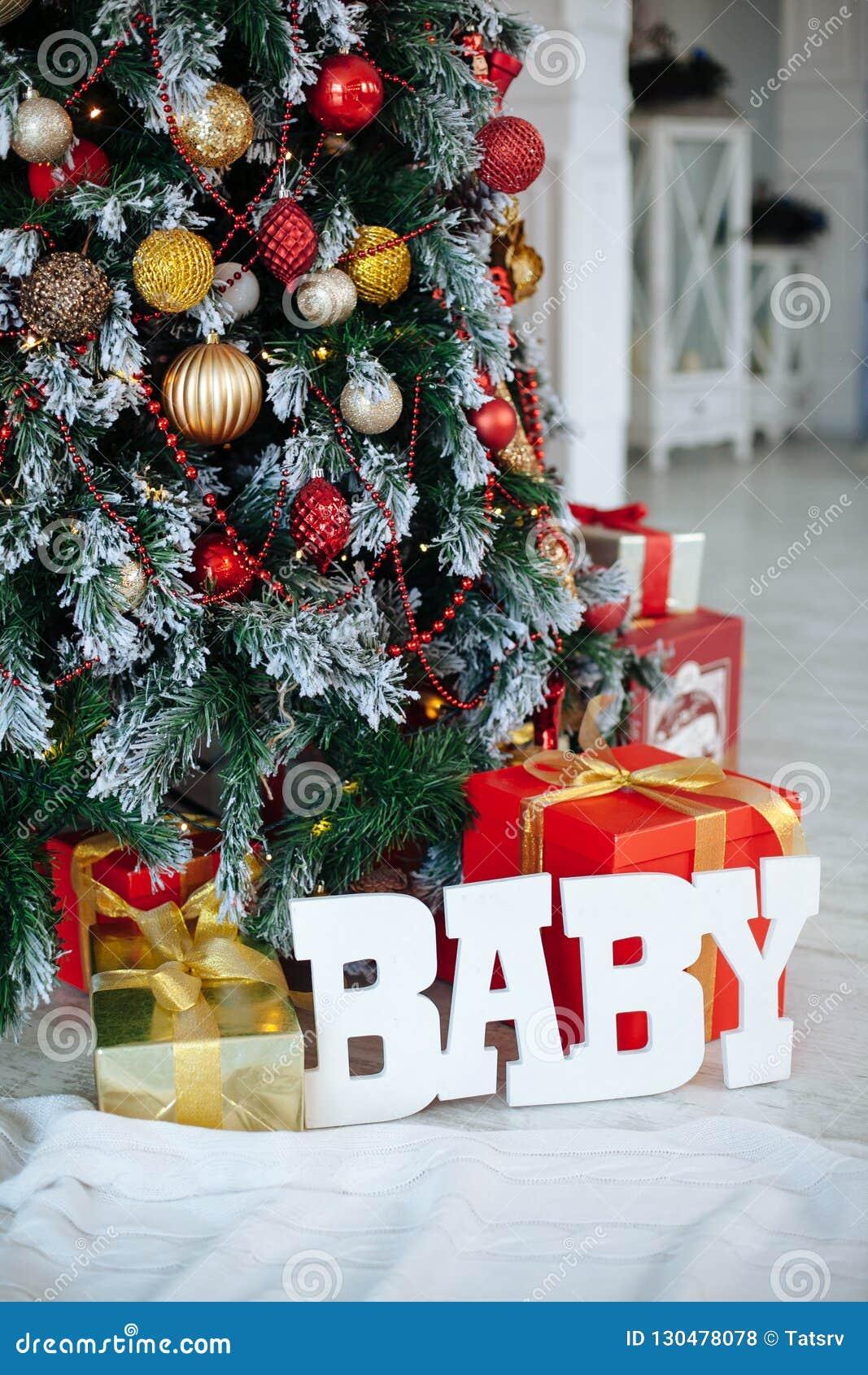 Cadeaux de Noël enveloppés dans le papier rouge classique et le BÉBÉ en bois de lettres, fond avec l arbre de Noël Copiez l espac