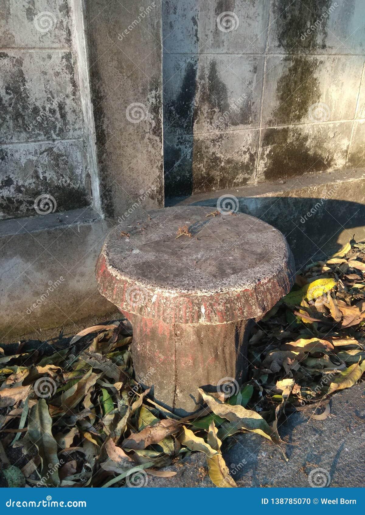 Cadeira do cimento do círculo ao lado da parede