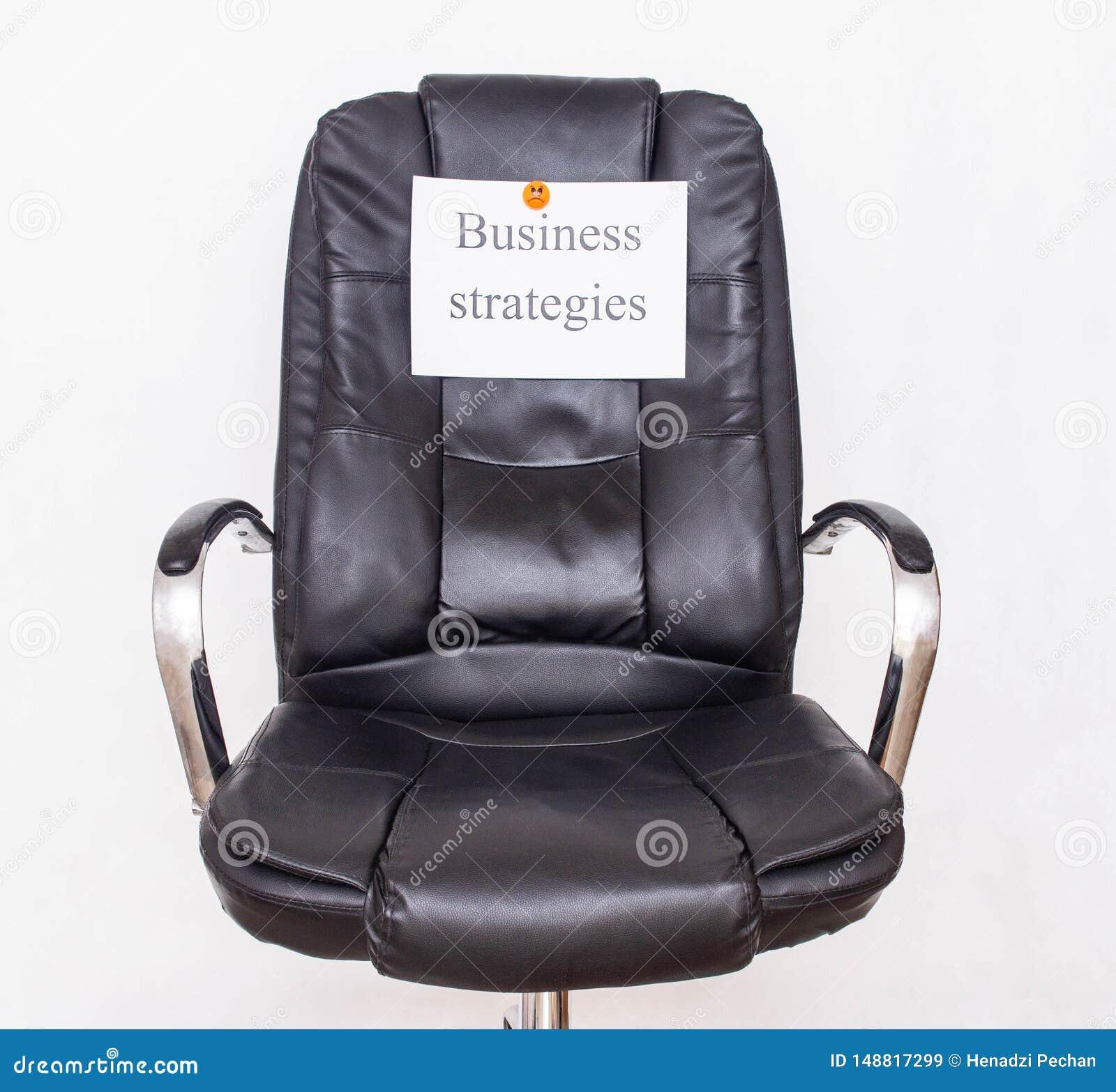 Cadeira do escrit?rio em que um peda?o de papel com o conceito da gest?o de estrat?gia empresarial da inscri??o e os tipos de inc