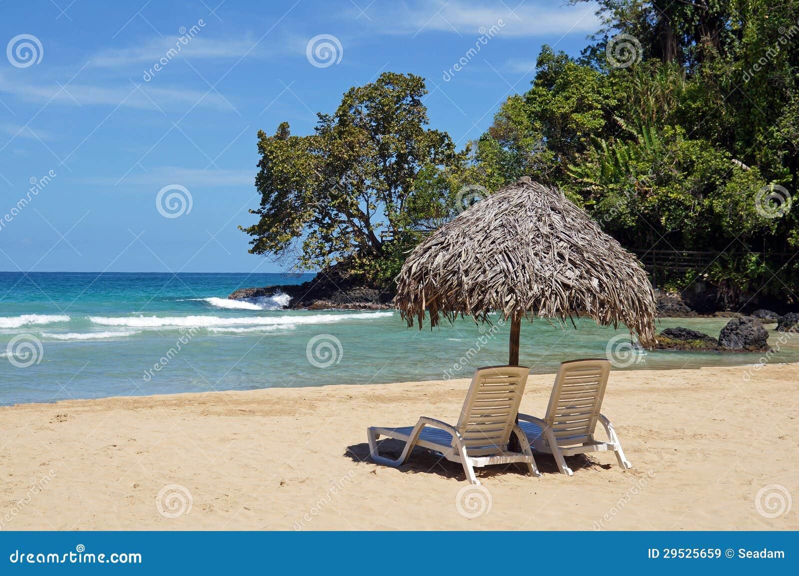 A cadeira e o guarda-chuva de praia na areia tropical idílico encalham