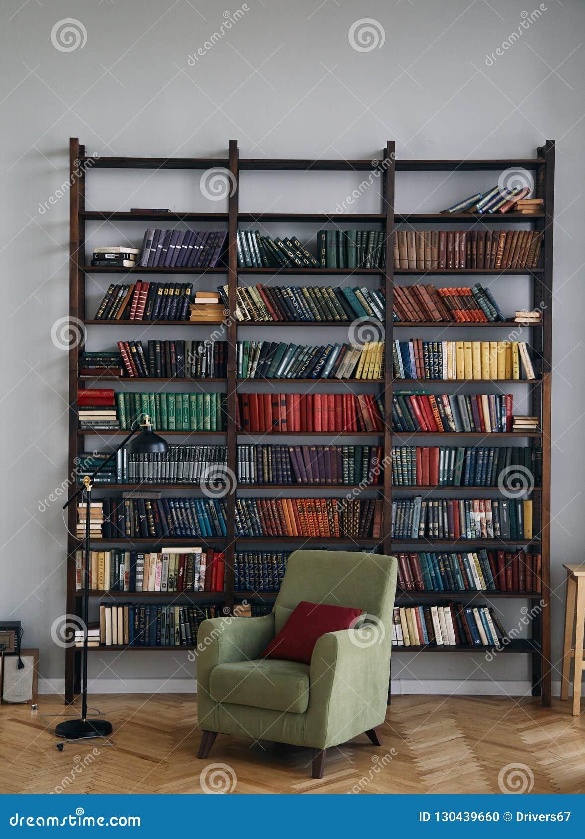 Cadeira verde no interior Biblioteca com os livros velhos nas prateleiras Livros em um armário de madeira velho