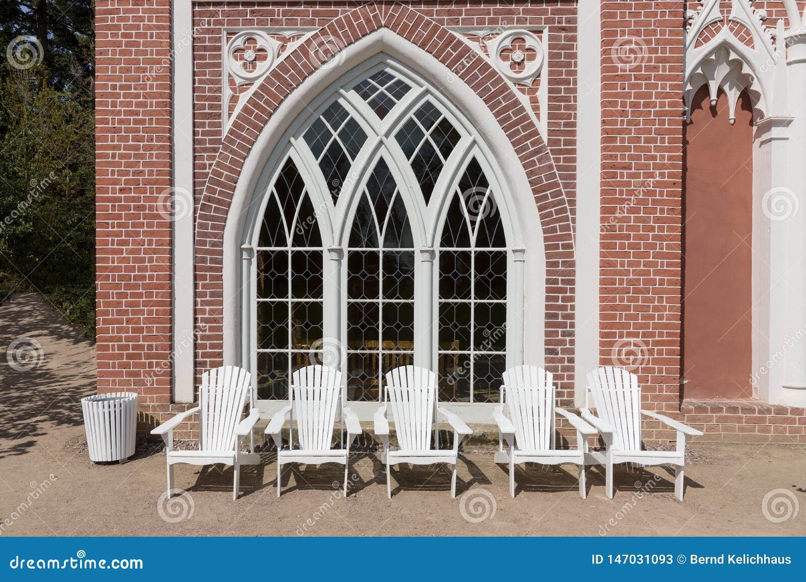 Cadeiras brancas a descansar na frente da casa de campo
