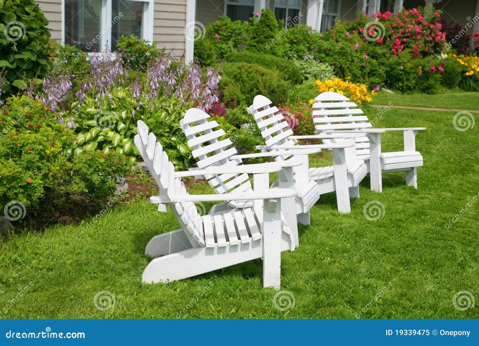 Cadeiras de jardim de madeira em um jardim do verão completamente dos  #4A6714 1300x957