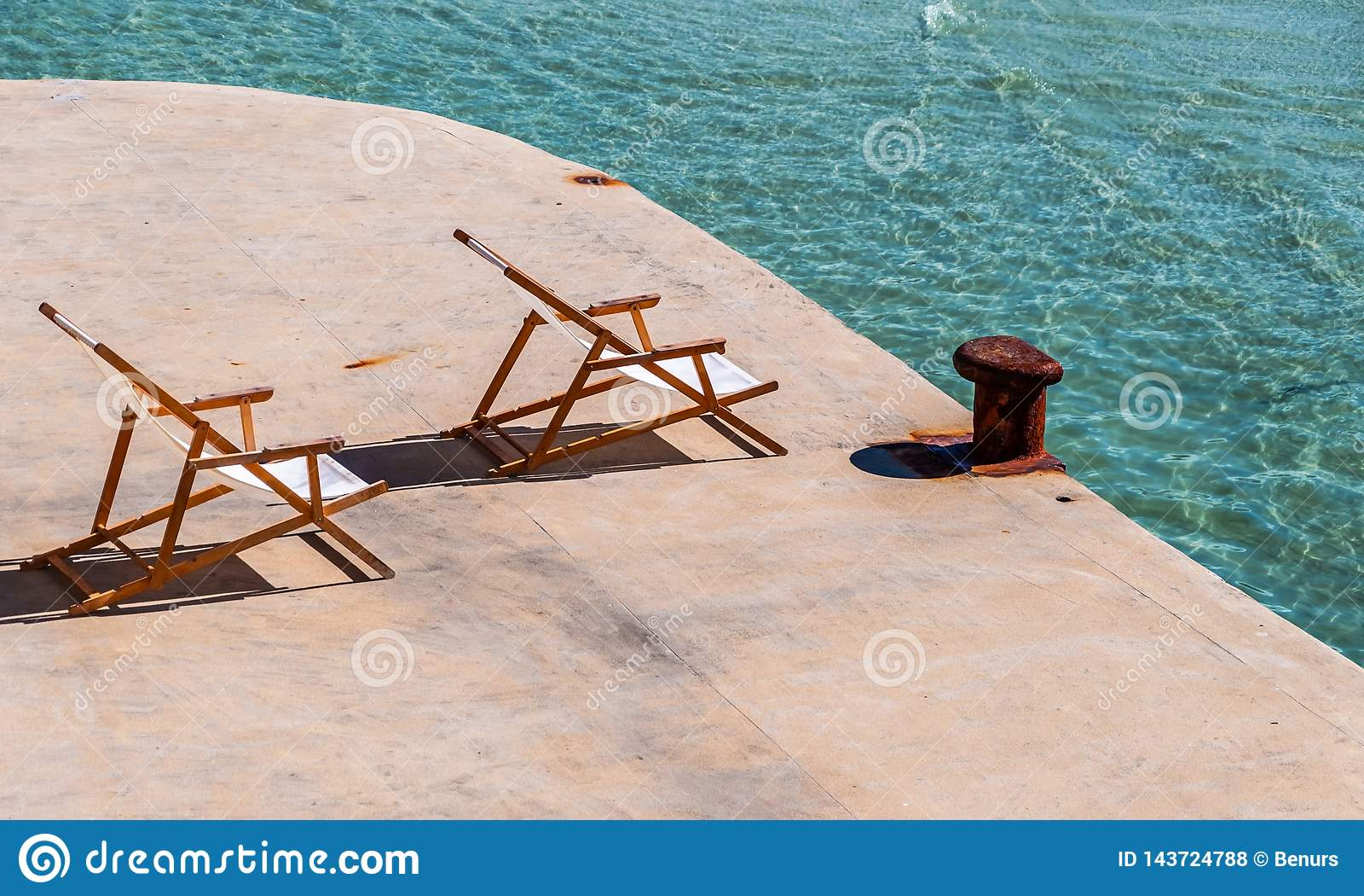 Cadeiras de plataforma da praia que enfrentam o sol no mar de turquesa e no poste de amarração oxidado
