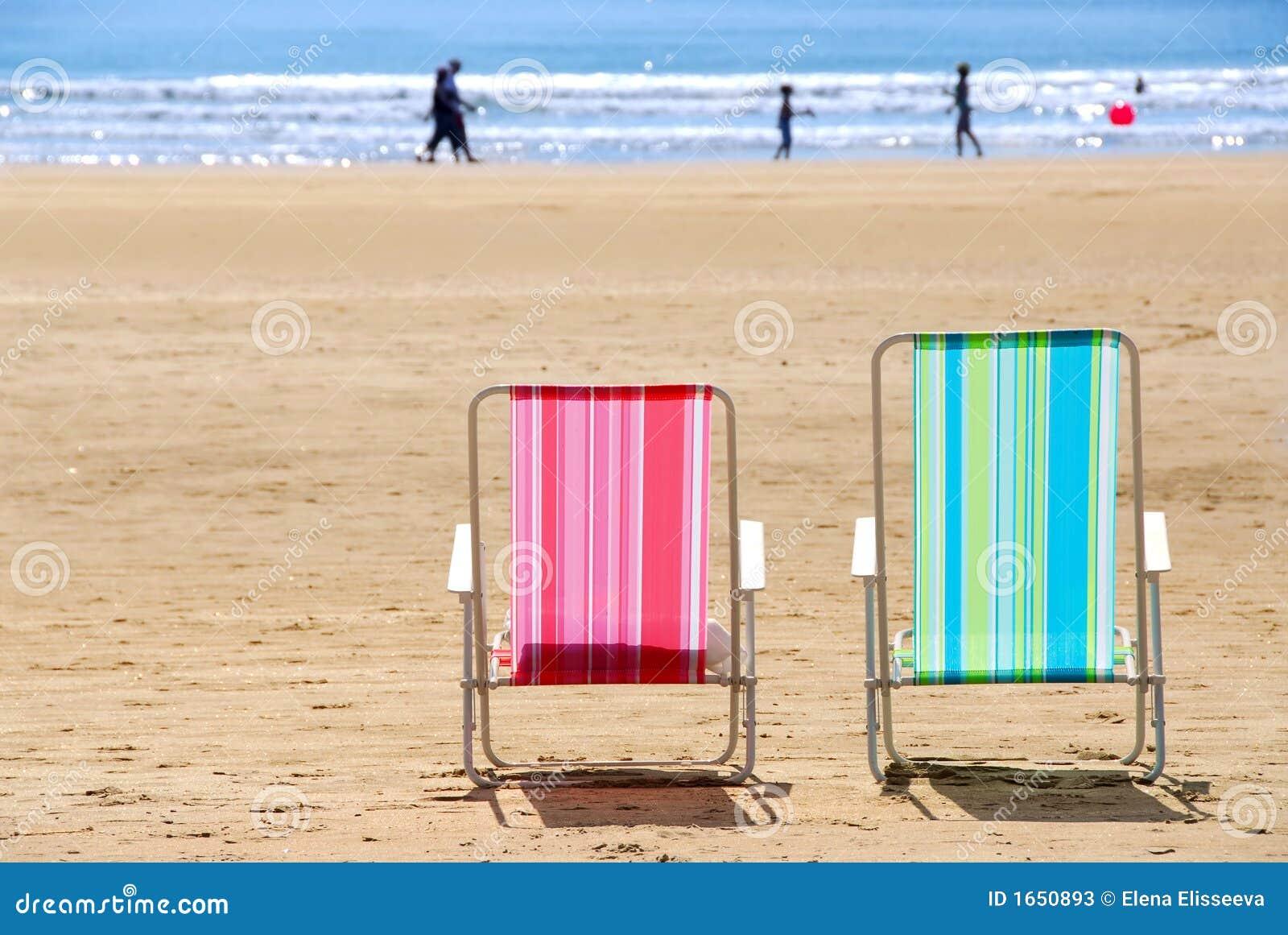 Duas cadeiras de praia coloridas vazias em uma praia arenosa. #C00B33 1300x960