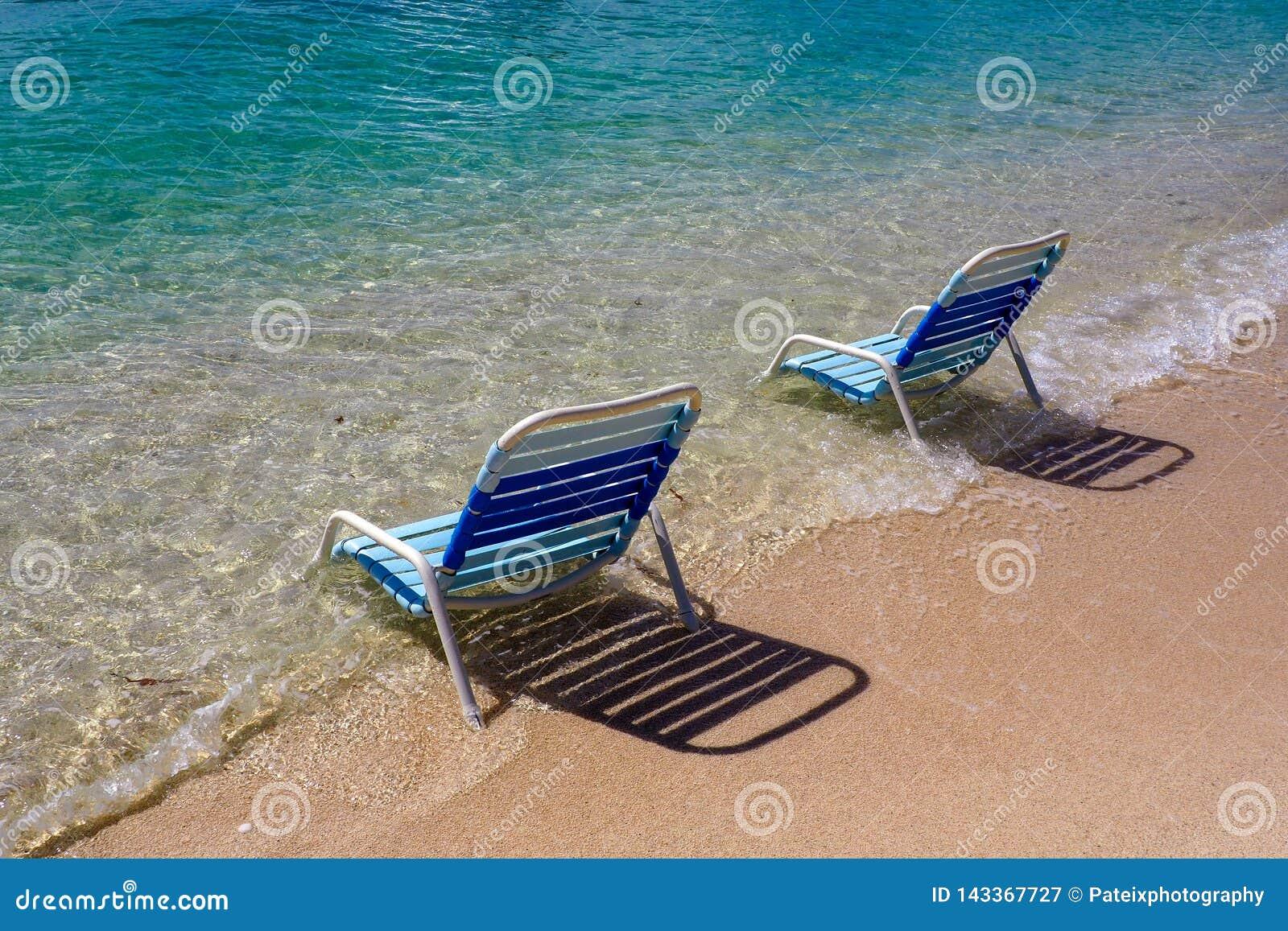 Cadeiras de praia azuis no mar na praia em Roatan