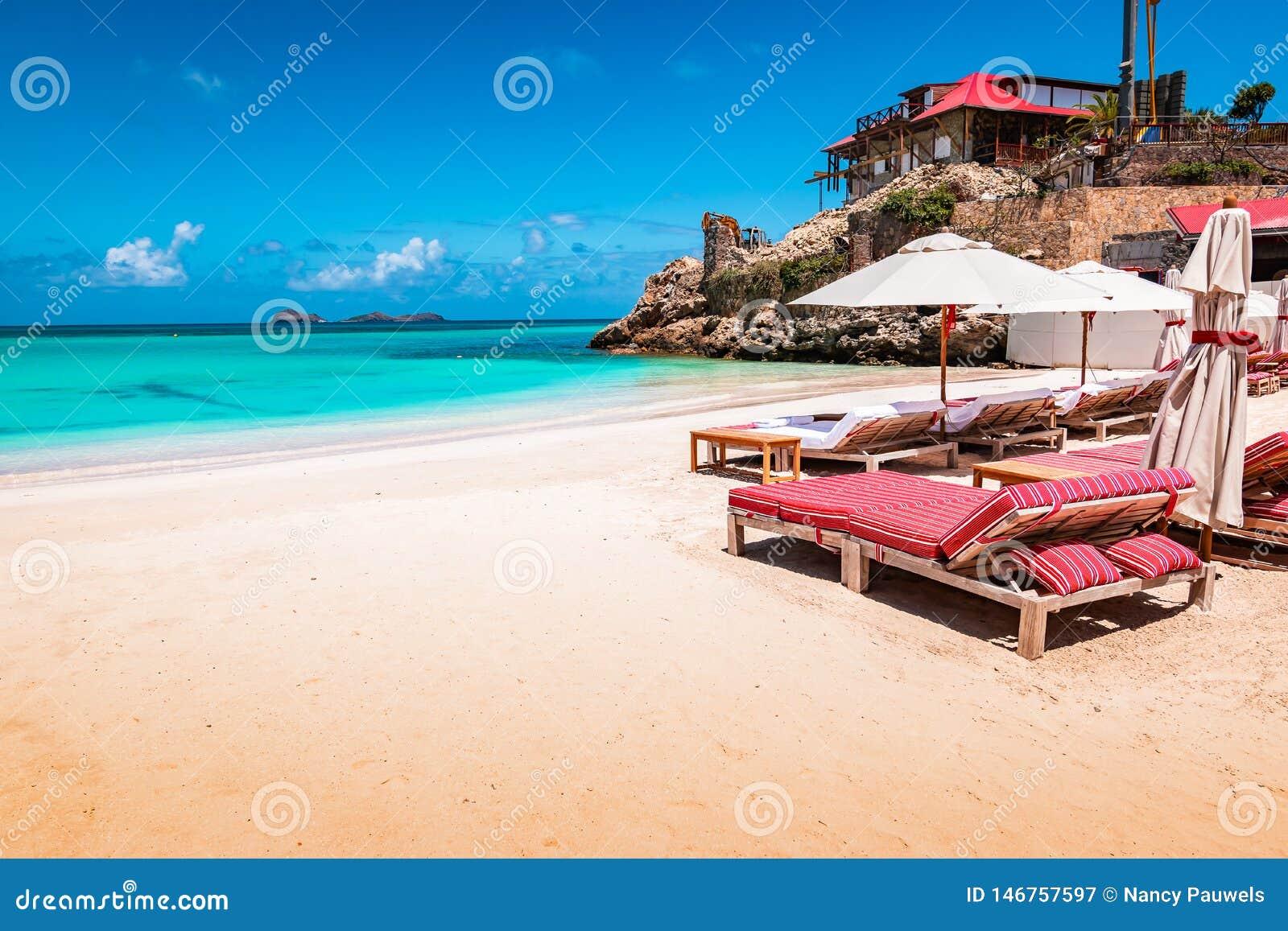 Cadeiras e guarda-chuva luxuosos de praia na praia exótica em St Barths, ilha das Caraíbas