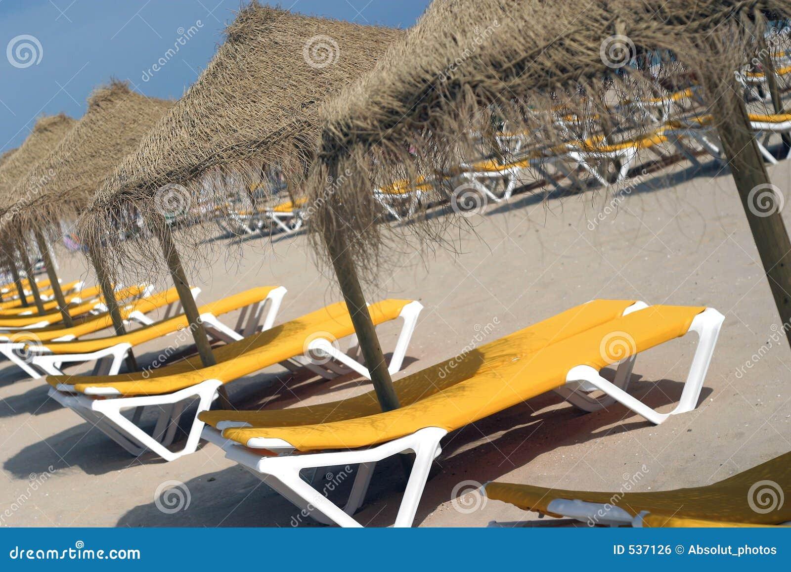 Cadeiras e guarda-chuvas de praia.
