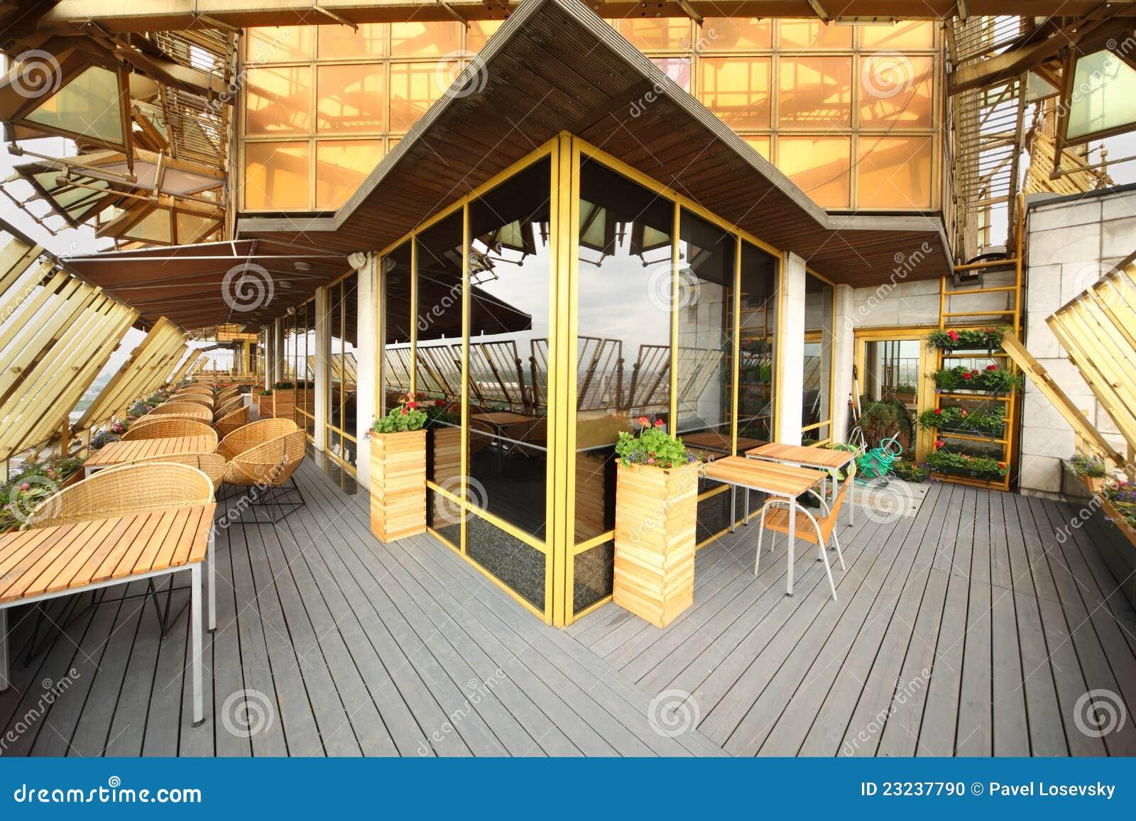 Cadeiras de madeira e de vime e tabelas no terraço no restaurante  #B68815 1300x957