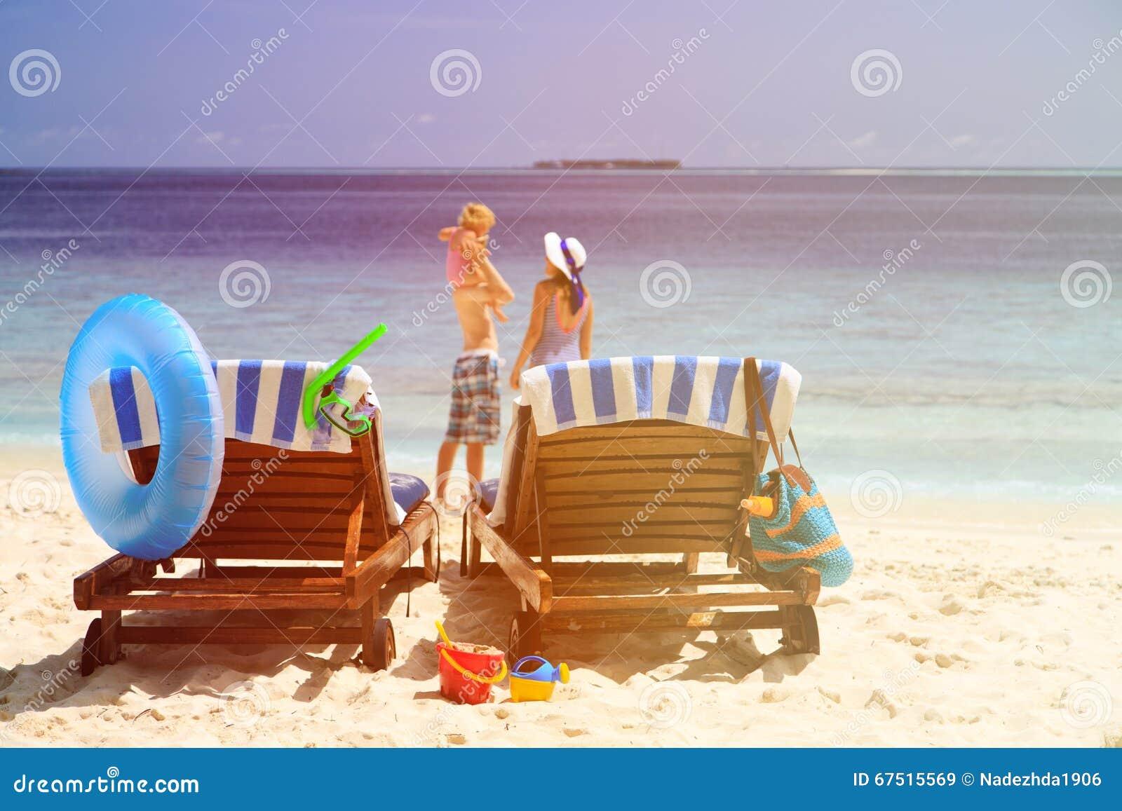Cadeiras na praia tropical, férias da praia da família