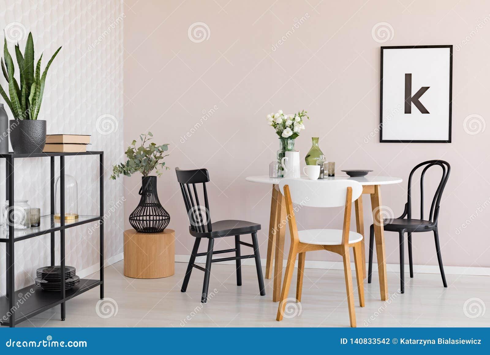 Cadeiras na tabela de madeira com as flores na sala de jantar interior com plantas e cartaz Foto real