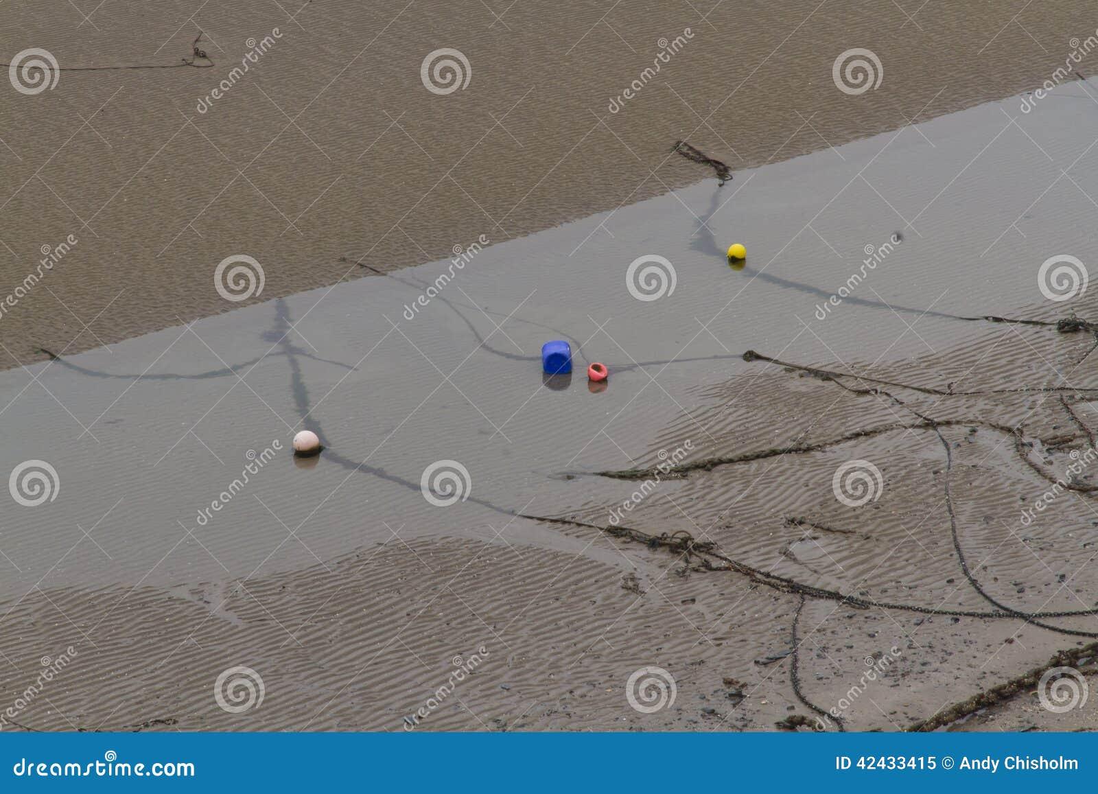 Cadenas del amarre, cuerdas y boyas, playa durante la bajamar