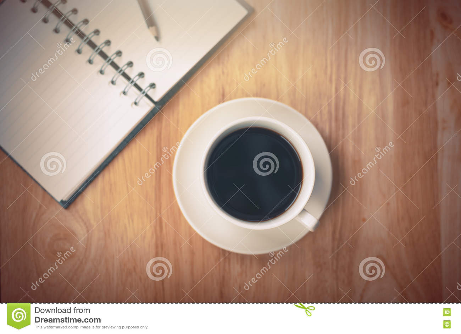 Caderno aberto do café preto com o lápis na tabela de madeira