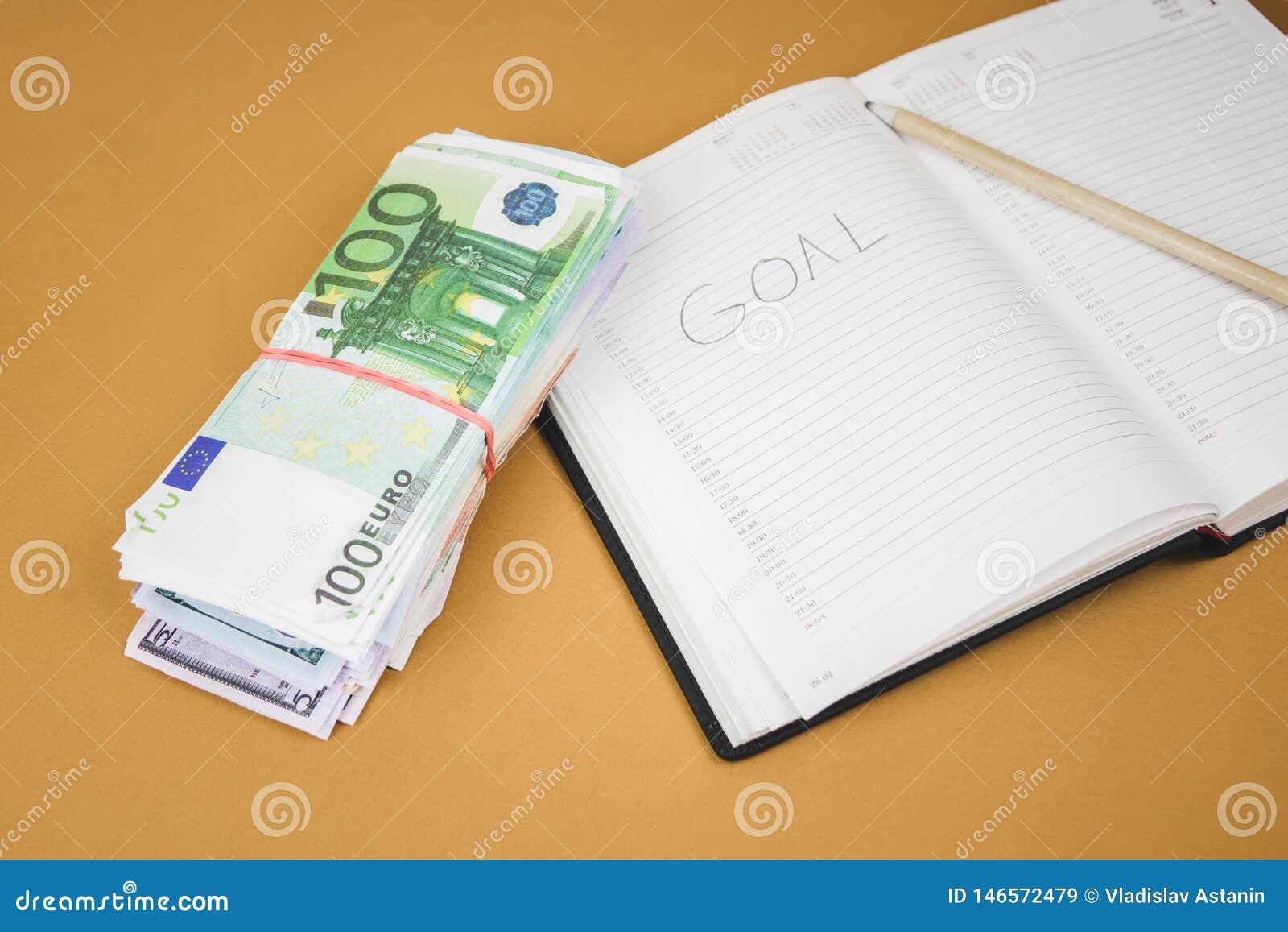 Caderno branco em de madeira o fundo de cem fins do dinheiro do euro acima