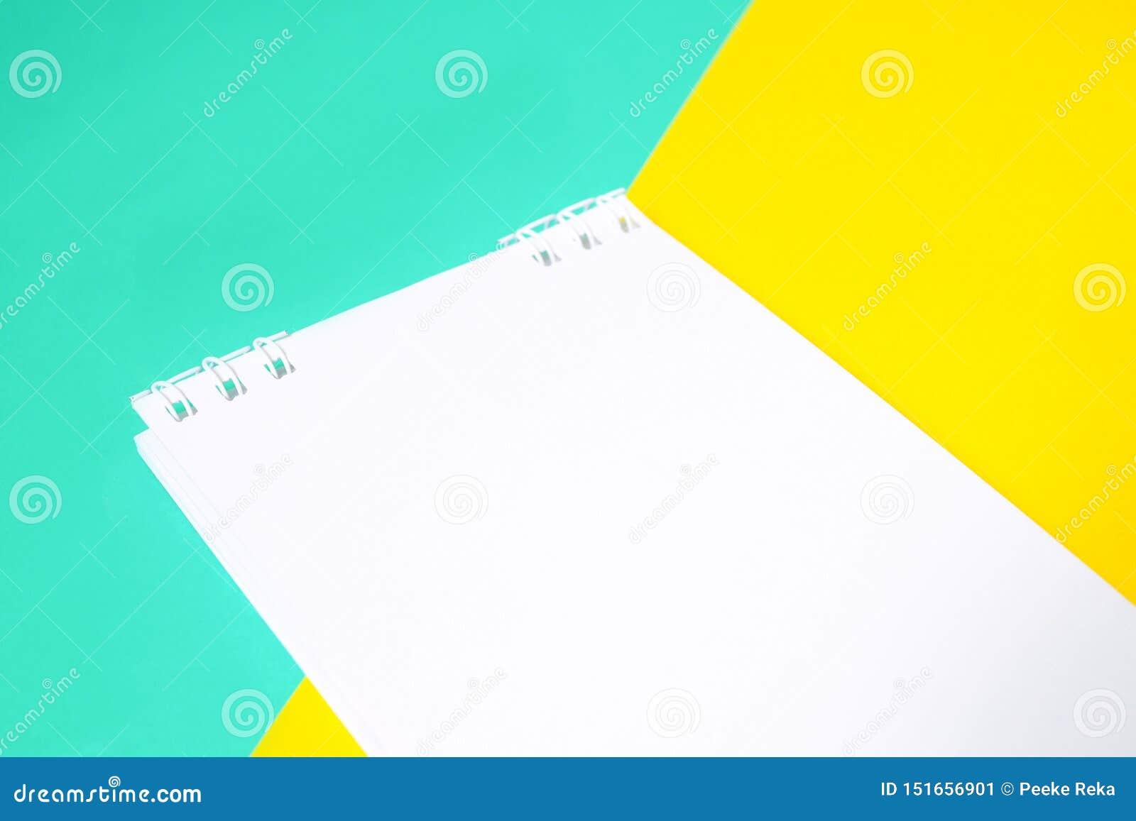 Caderno com Livro Branco no fundo multi-colorido com amarelo e o azul