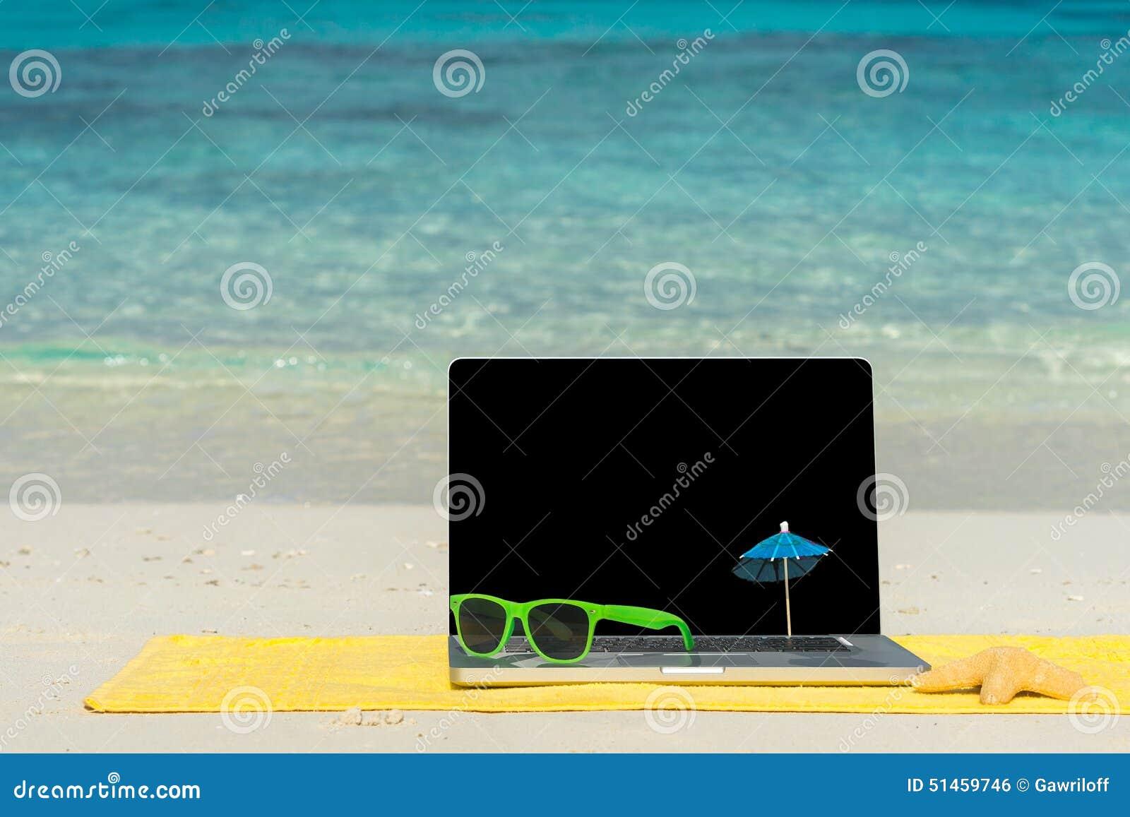 Caderno do computador na praia - fundo da viagem de negócios