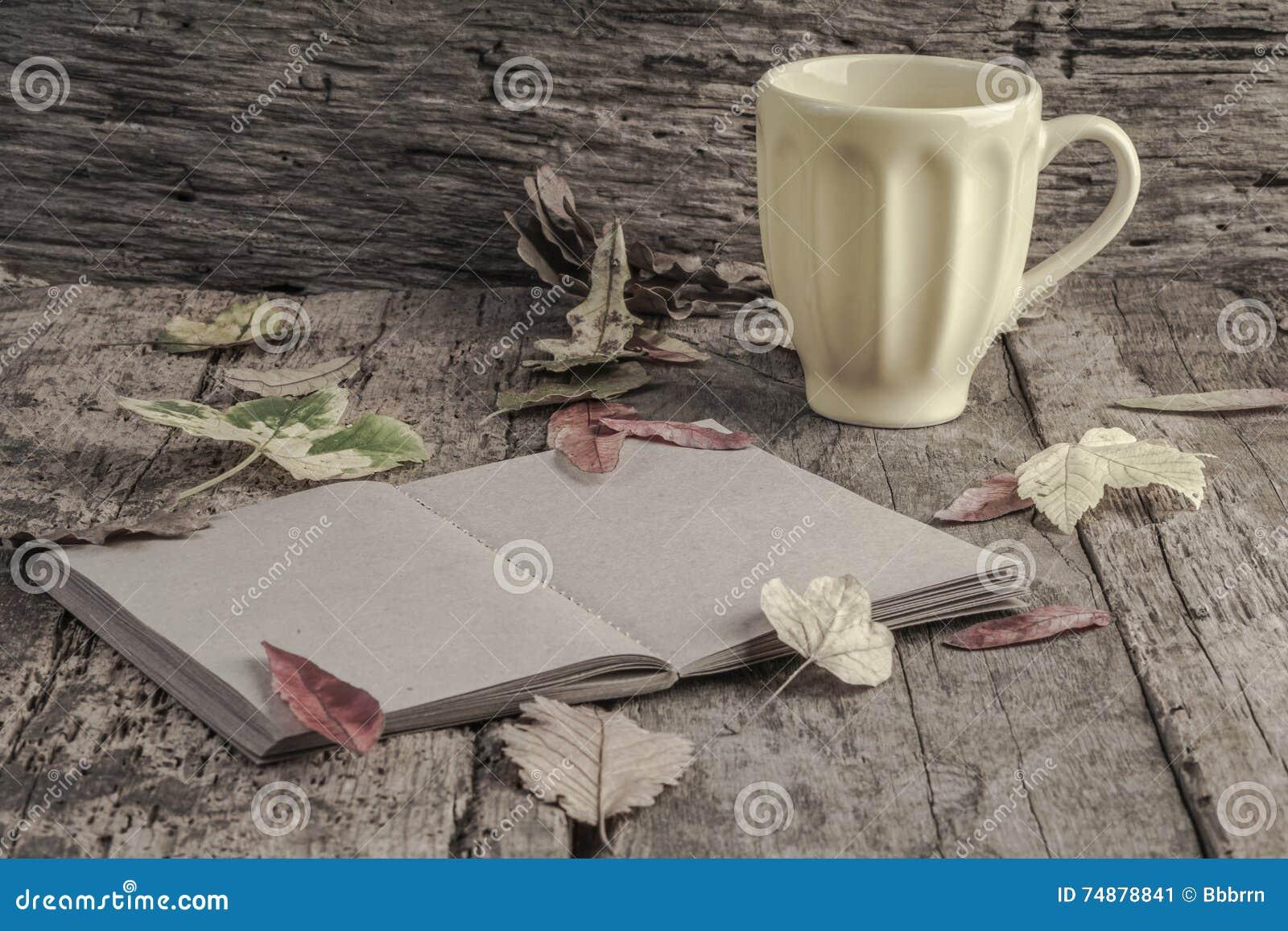 Caderno e café na tabela de madeira decorada com folhas secadas