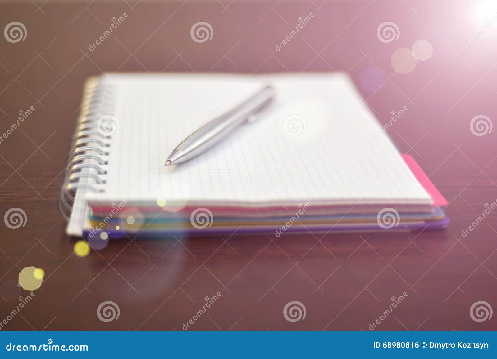 Caderno e pena de aço na tabela com luz solar