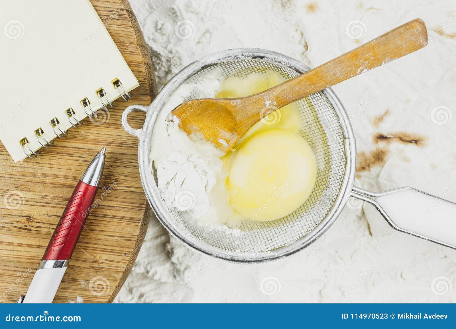 Caderno para receitas, ovo, colher de madeira em um fundo da farinha