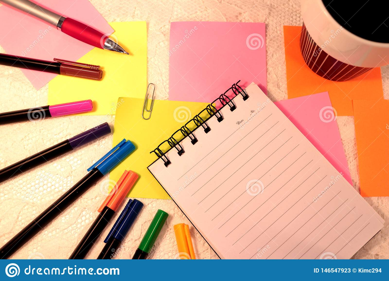 Caderno, penas de feltro em várias cores, notas pegajosas e uma xícara de café