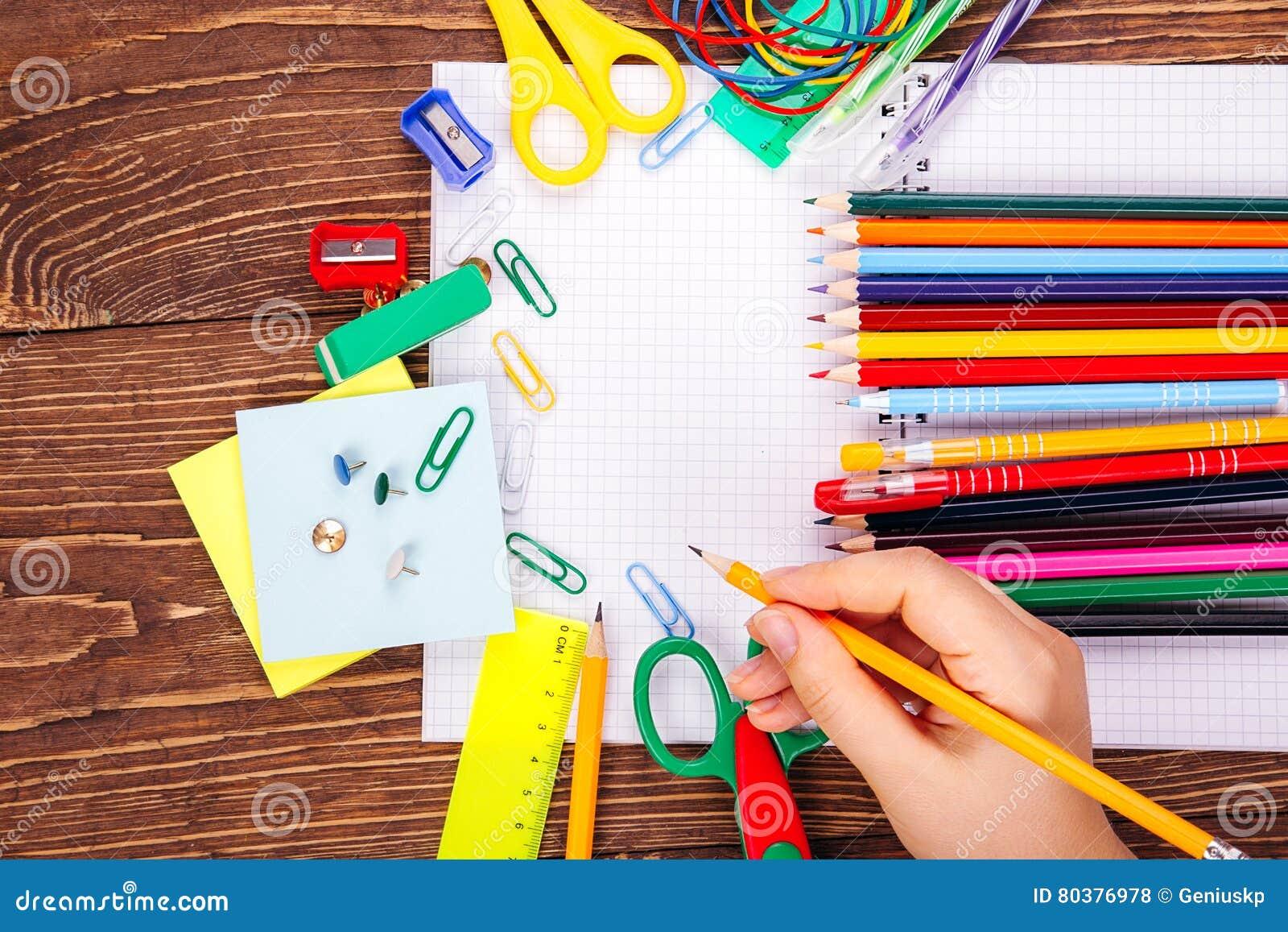 Caderno vazio aberto, mão com um quadro do brushwith do sup da escola
