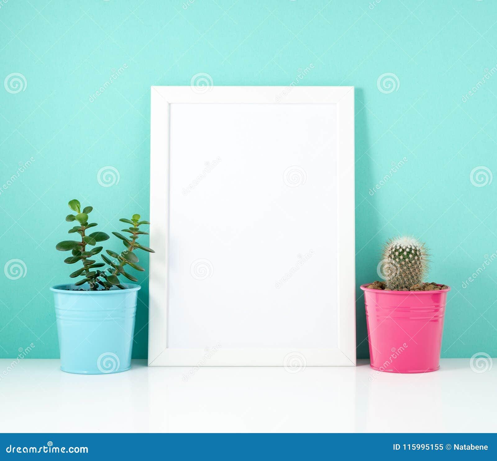 Cadre blanc vide, cactus d usine sur la table blanche contre le mur bleu Maquette avec l espace de copie