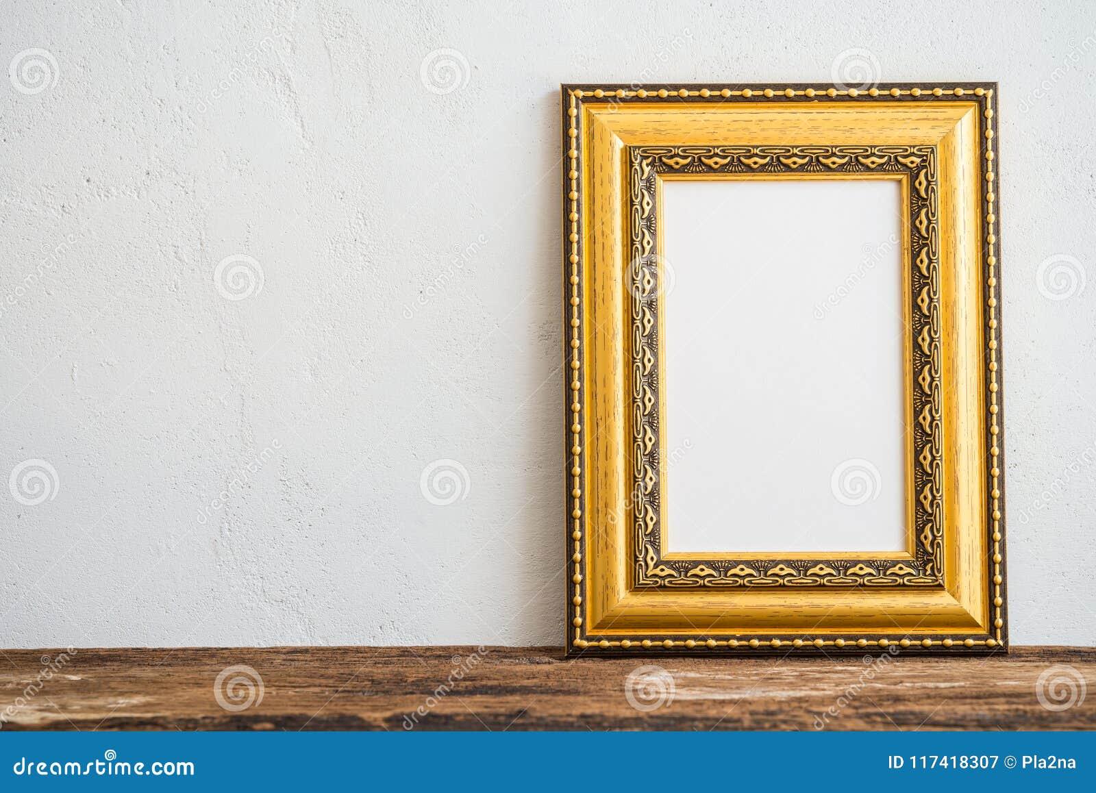 Cadre d or de photo de vintage sur la vieille table en bois au-dessus du mur blanc b
