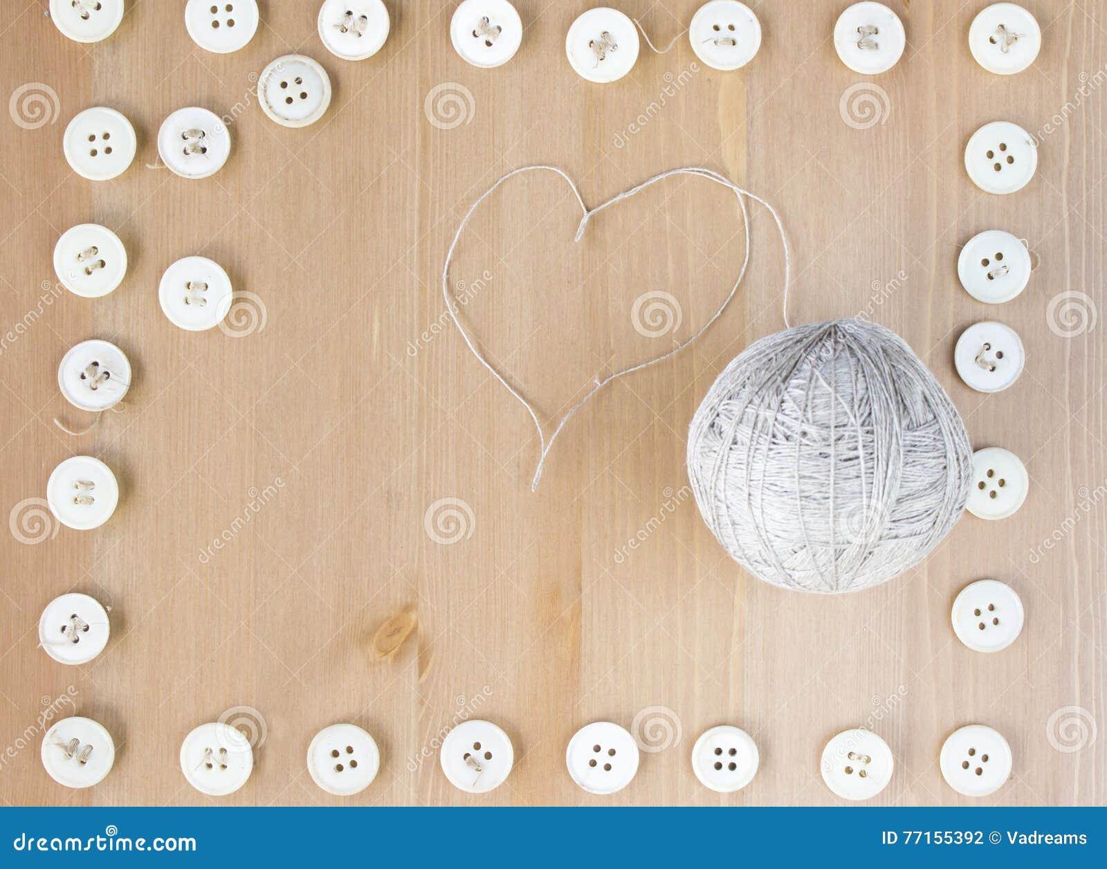 Cadre de boutons de vintage et boule de couture du fil en forme de coeur de toile au milieu Configuration plate, vue supérieure C