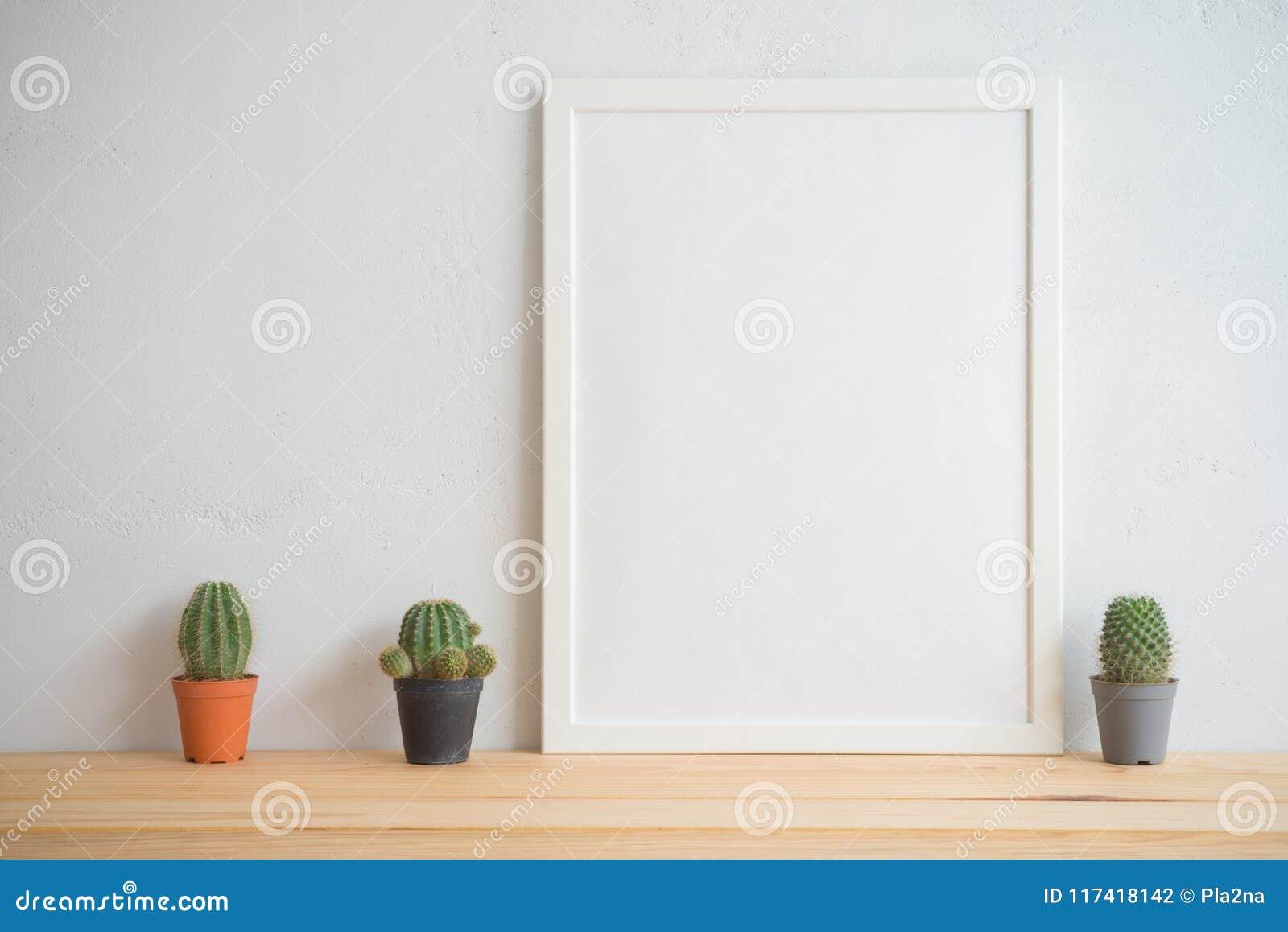 Cadre de photo et maquette de pots de cactus avec le fond blanc de mur, c