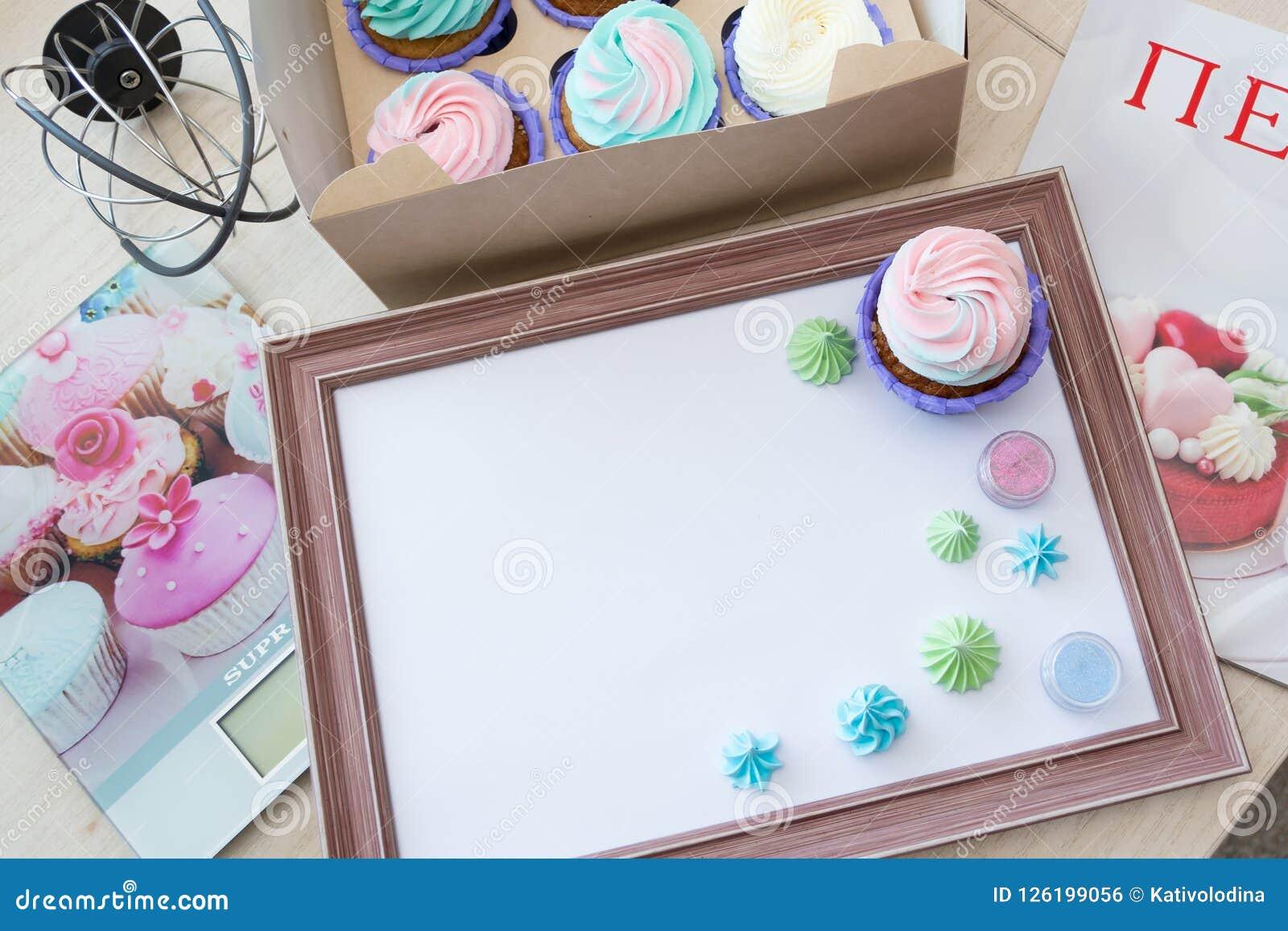 Cadre en bois avec la feuille blanche autour de la meringue et du petit gâteau avec de la crème multicolore, échelle de cuisine,