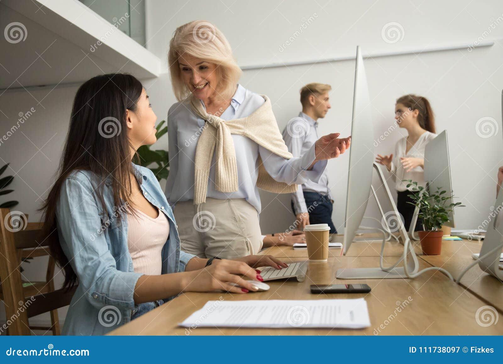 Cadre supérieur heureux de sourire parlant à l employé asiatique au travail