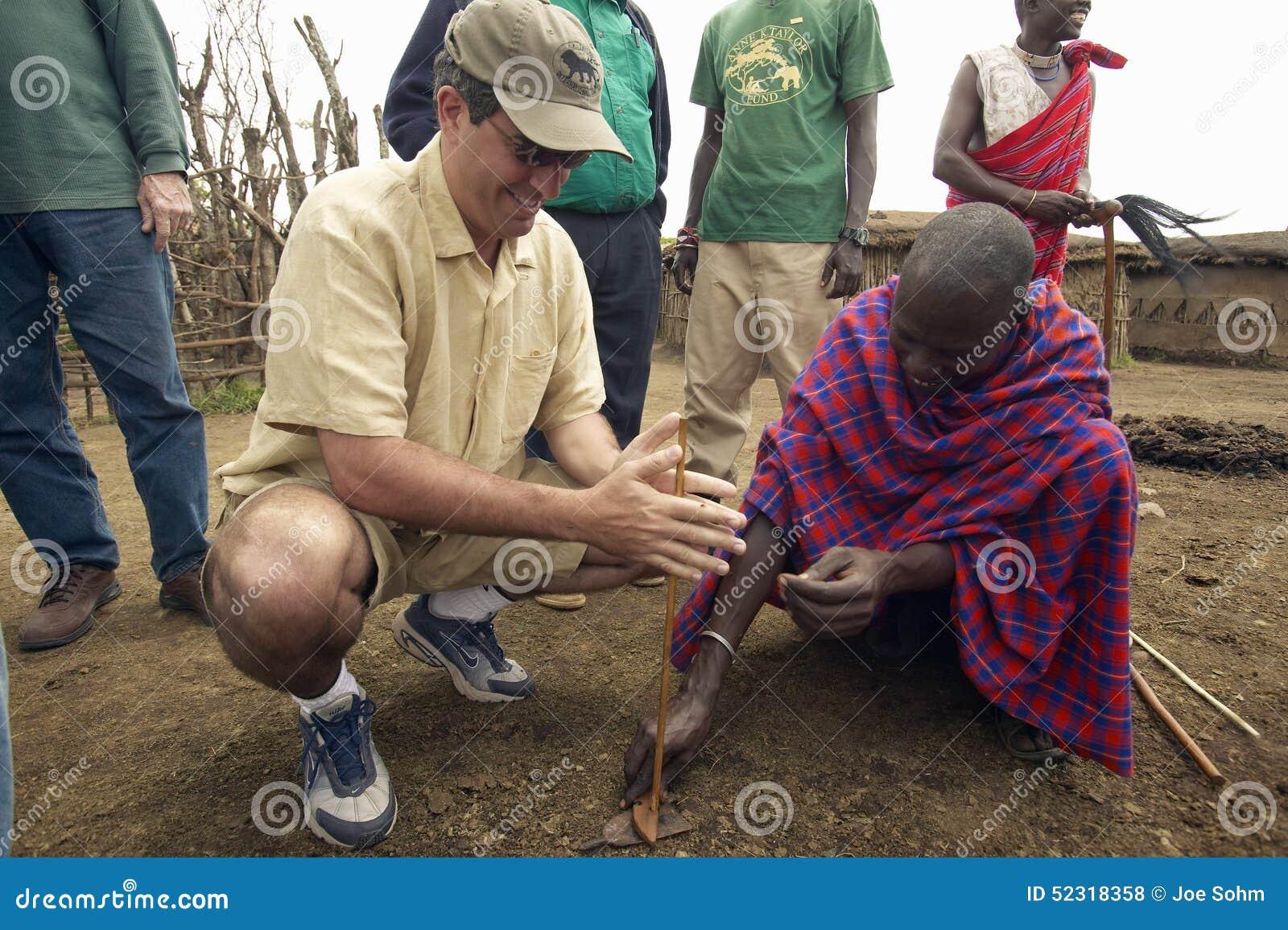 Cadre supérieur Officer, Wayne Pacelle de société humanitaire, apprenant à faire le feu à partir du membre de la tribu près du pa