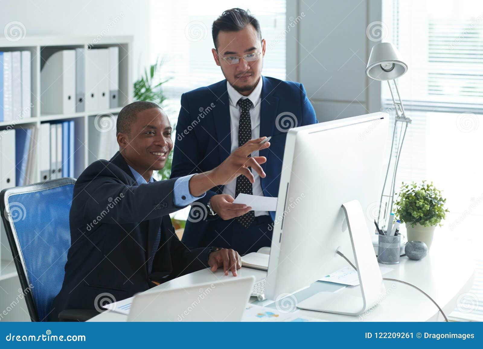 Cadres commerciaux lisant des données sur l écran d ordinateur
