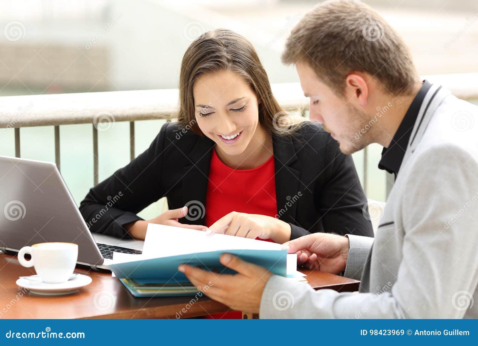 Cadres consultant des documents dans un café