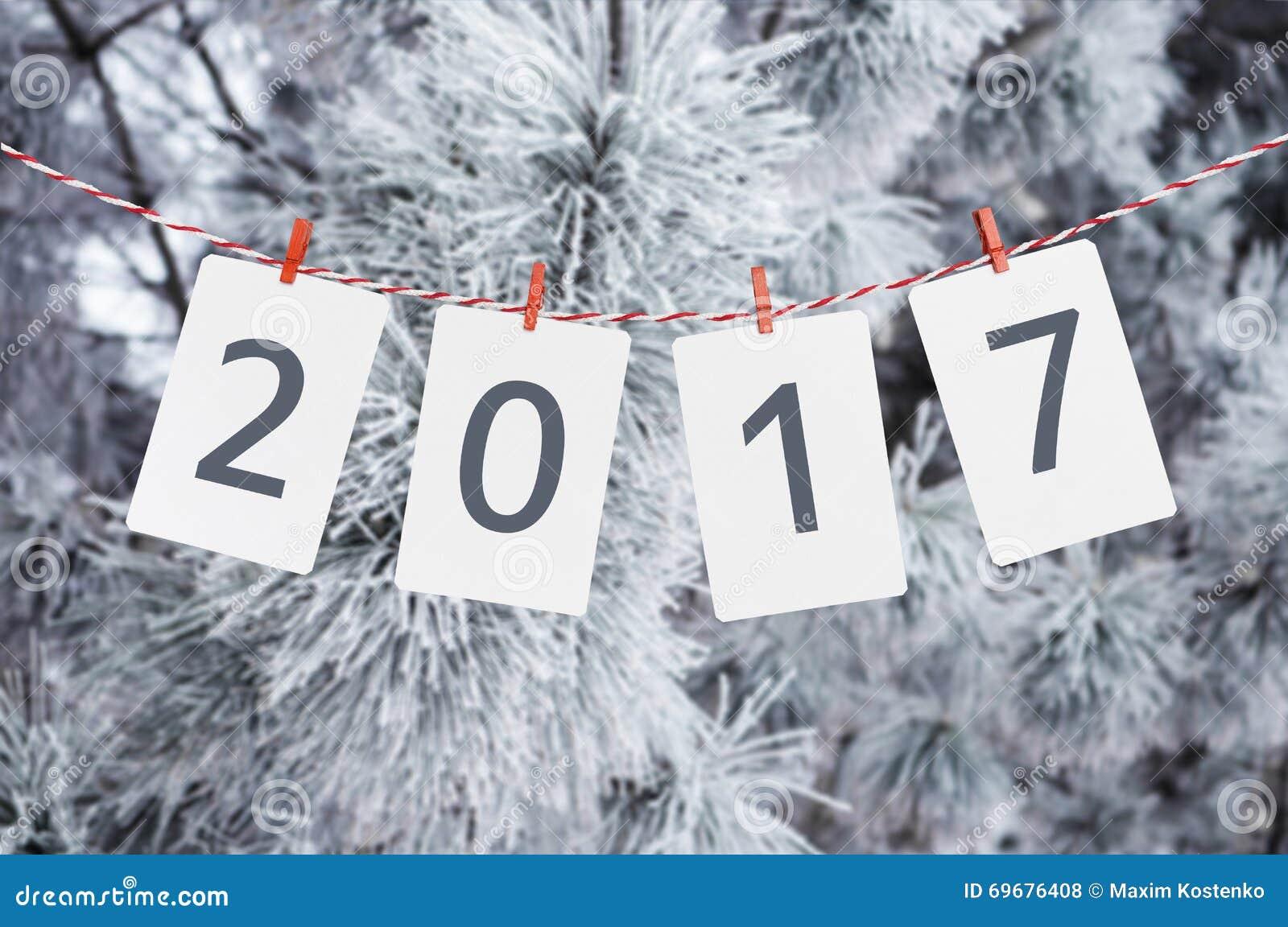 Cadres de papier ou de photo avec 2017 accrochant sur la corde rayée rouge Photo d un pin neigeux au fond an neuf de conception