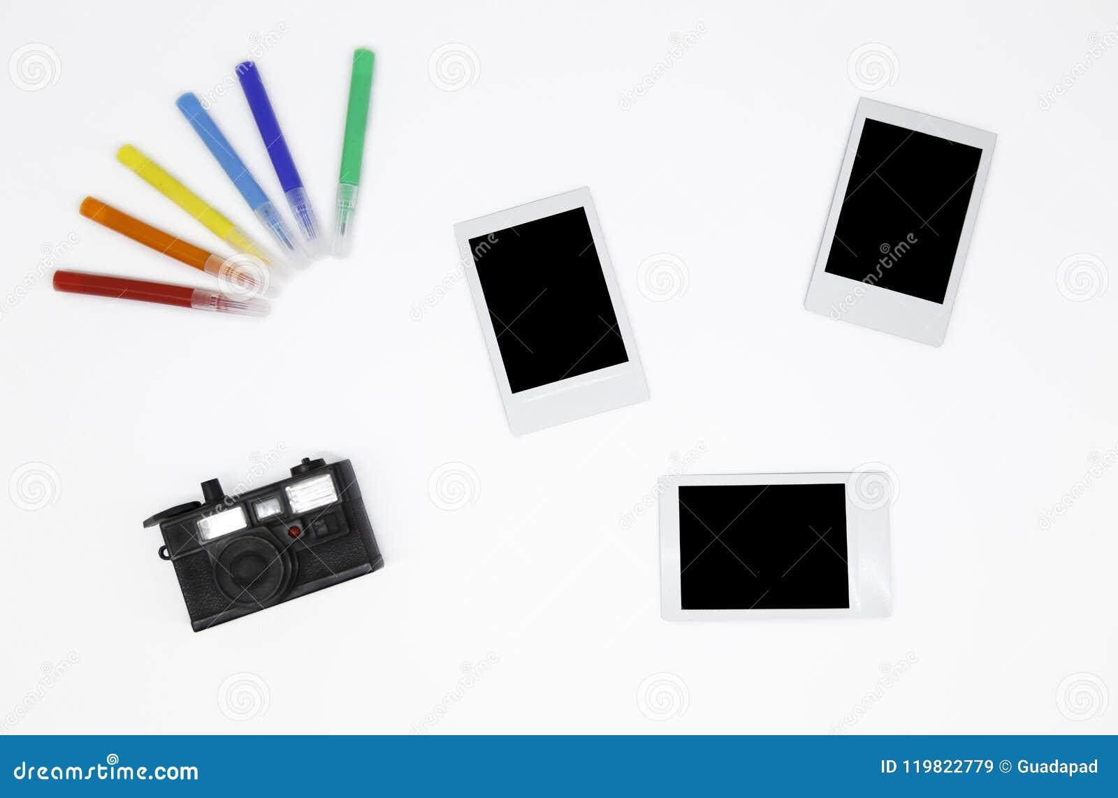 Cadres instantanés en blanc de photos du ` trois avec un mini appareil-photo et un ` coloré de marqueurs