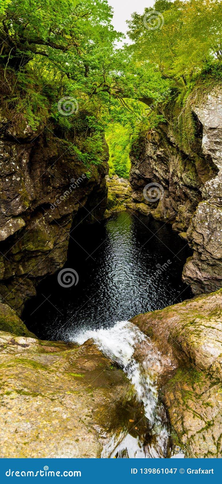 Cadute della cascata degli atrii in gola stretta con il vecchio ponte di pietra al lago Ness In Scotland