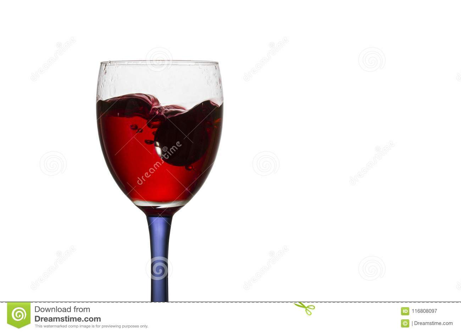 Caduto in un vetro del primo piano dell uva del vino rosso
