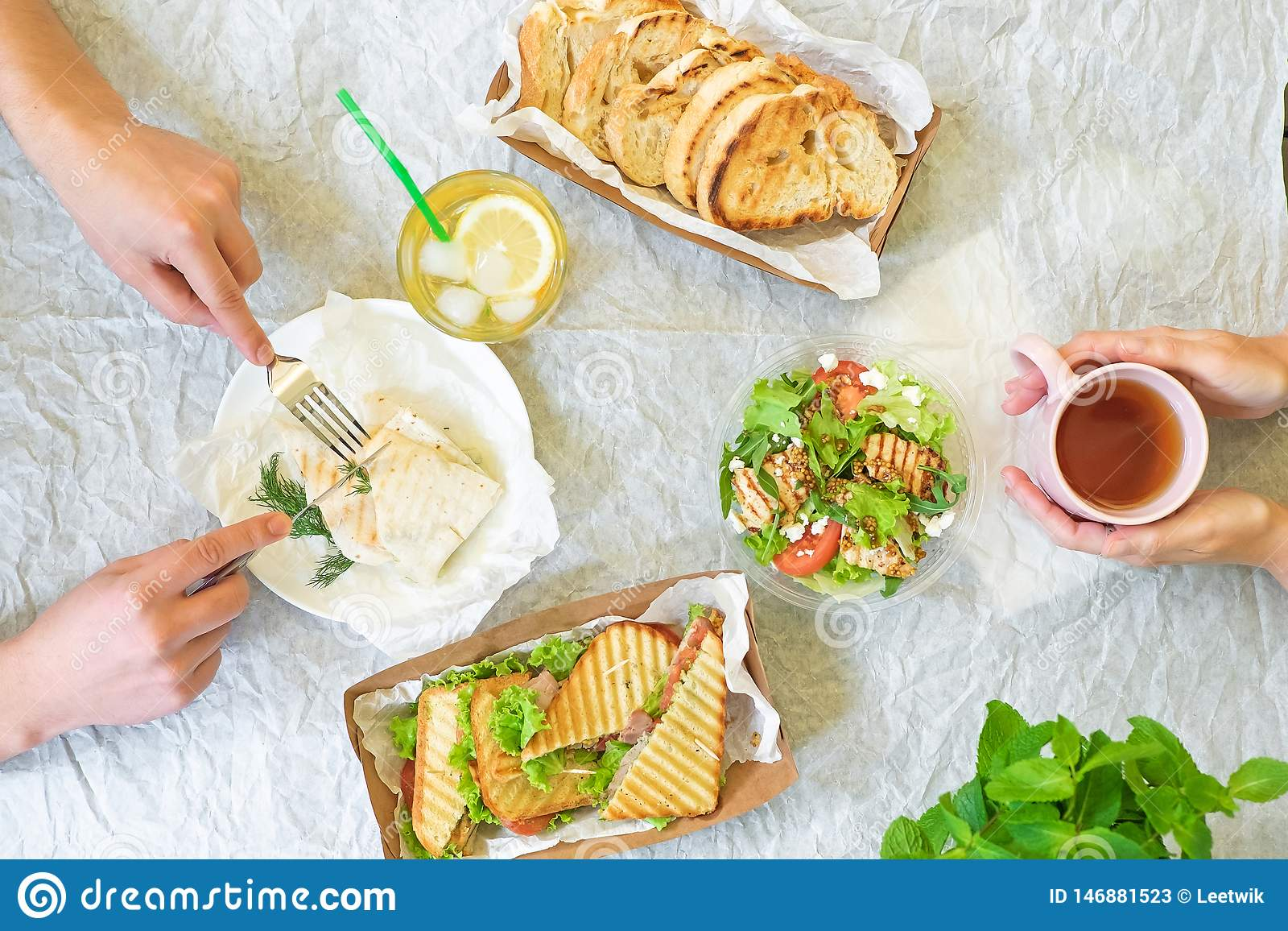 Caesar salad, bruschetta, ham and tomato sandwiches table with hands, top view from above