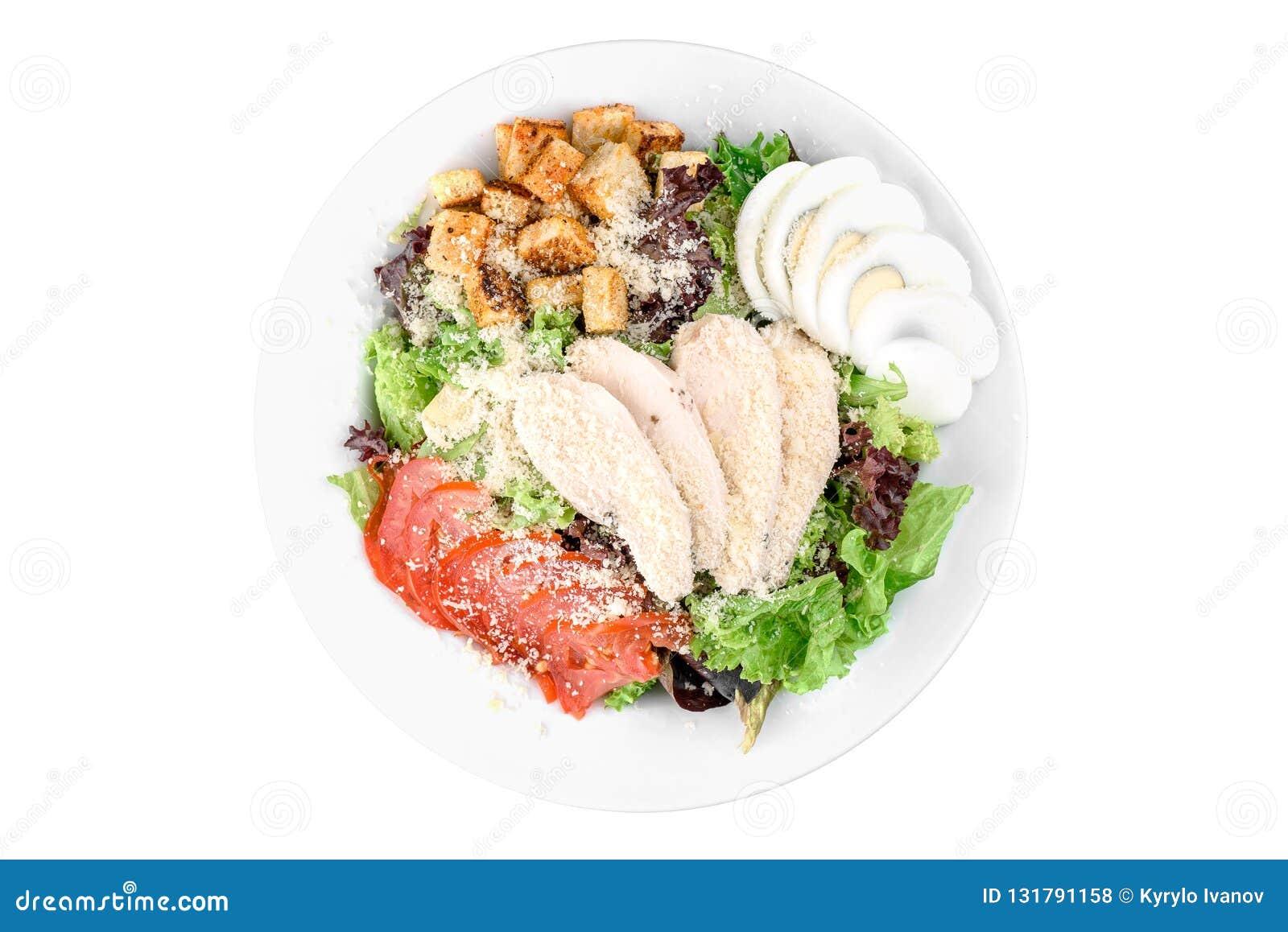 Caesar sallad med den fega filén, ägg, körsbärsröd tomat, vitt rostat bröd i en vit platta som isoleras på en vit bakgrund