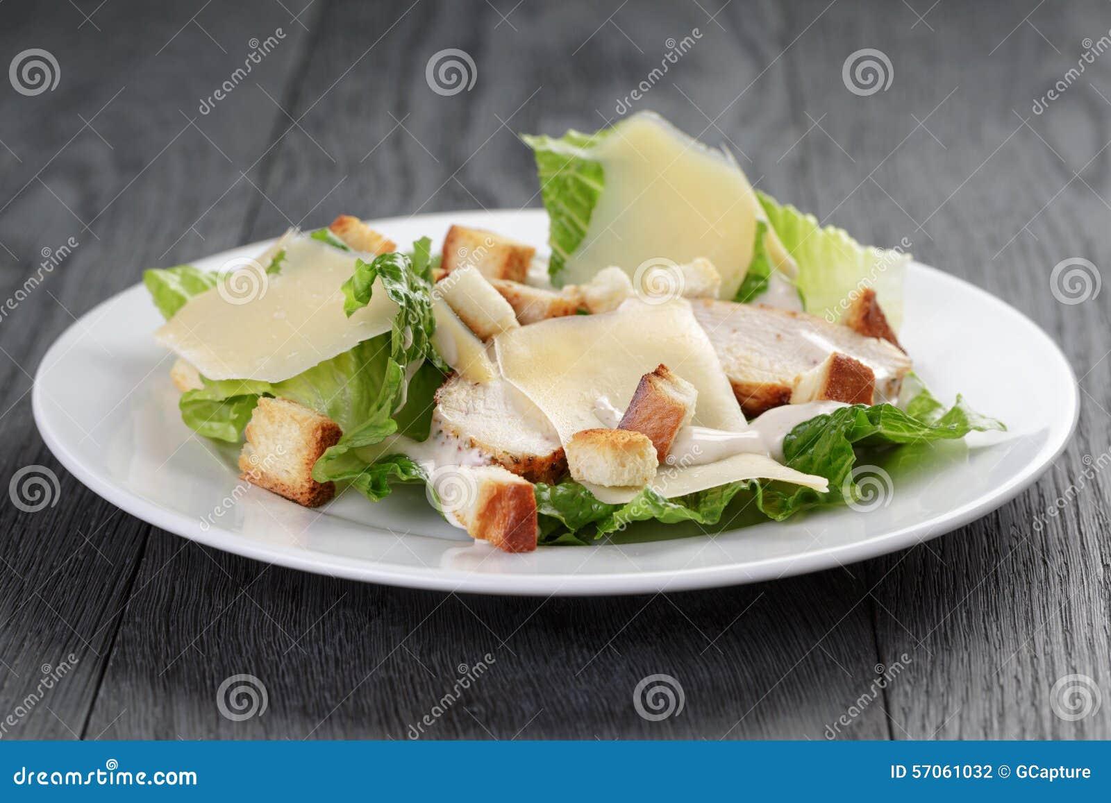 Caesarsalade met kip op eiken lijst