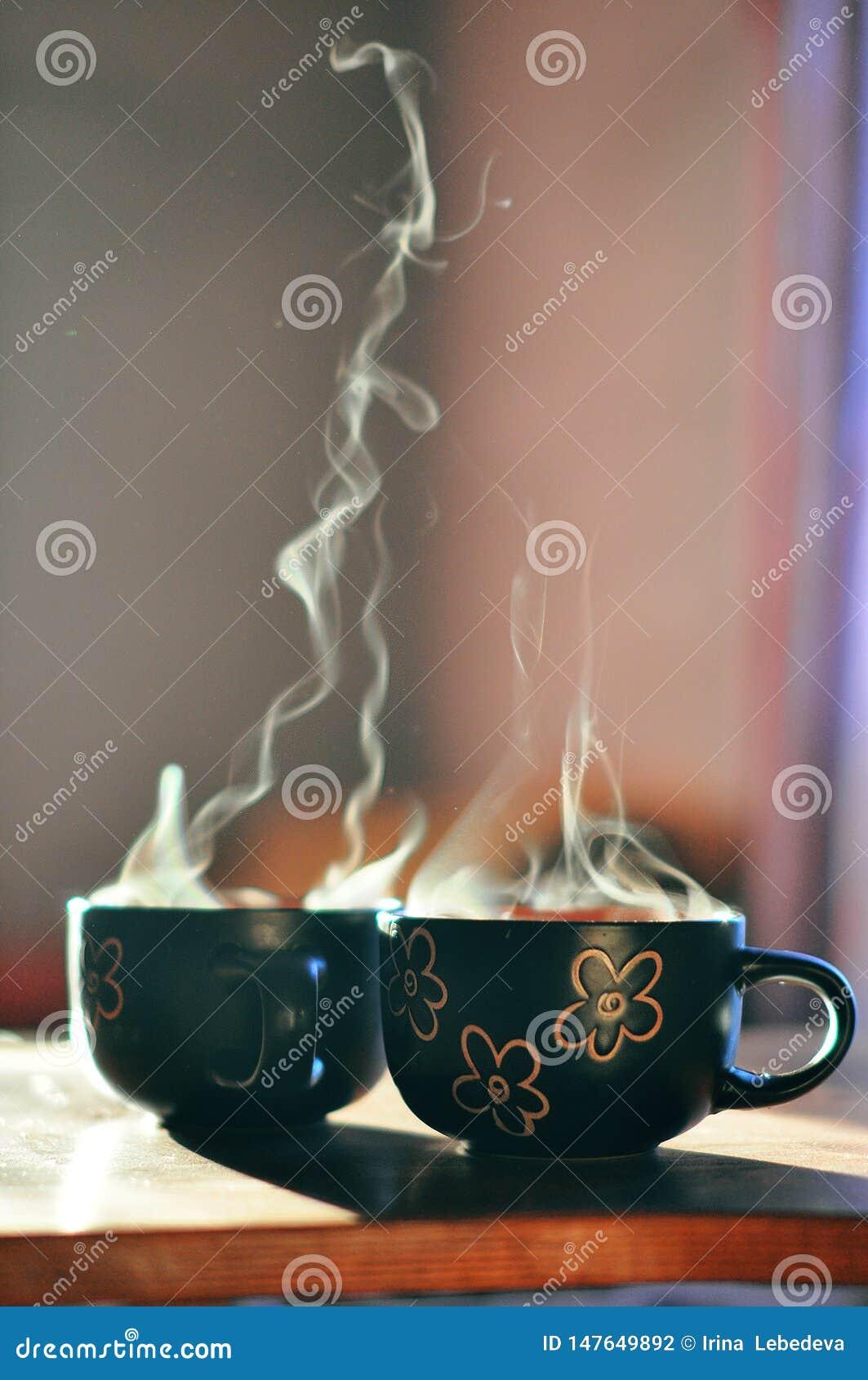 Café aromático en tazas en el sol de la mañana
