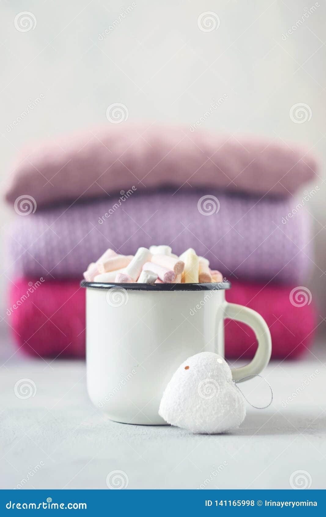 Café avec des guimauves à la tasse émaux blanche en métal et au coeur blanc sur le fond de la pile de chandails tricotés roses su