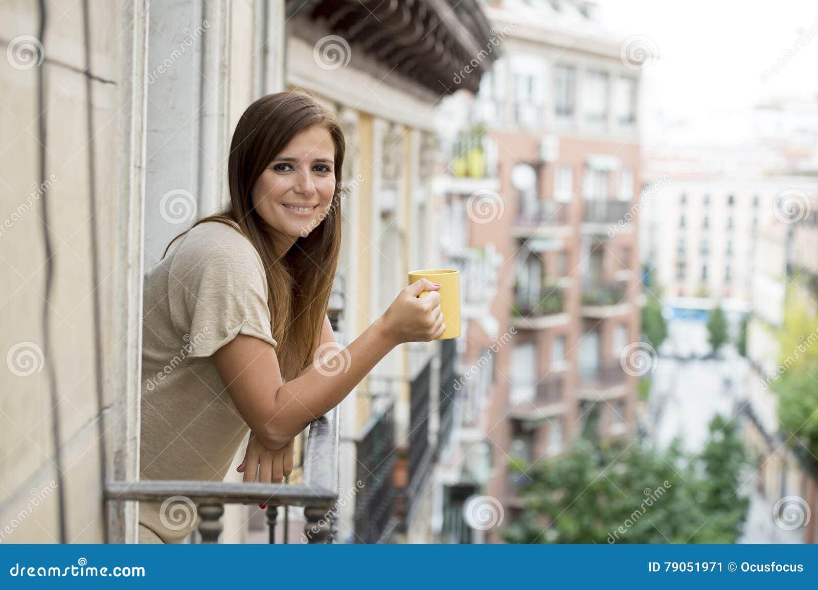 Café bebendo alegre relaxado do chá da mulher bonita no terraço do balcão do apartamento