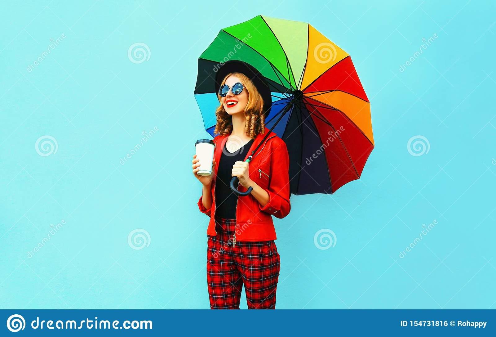 Café bebendo da jovem mulher e guardar o guarda-chuva colorido que anda no revestimento vermelho, chapéu negro na parede azul